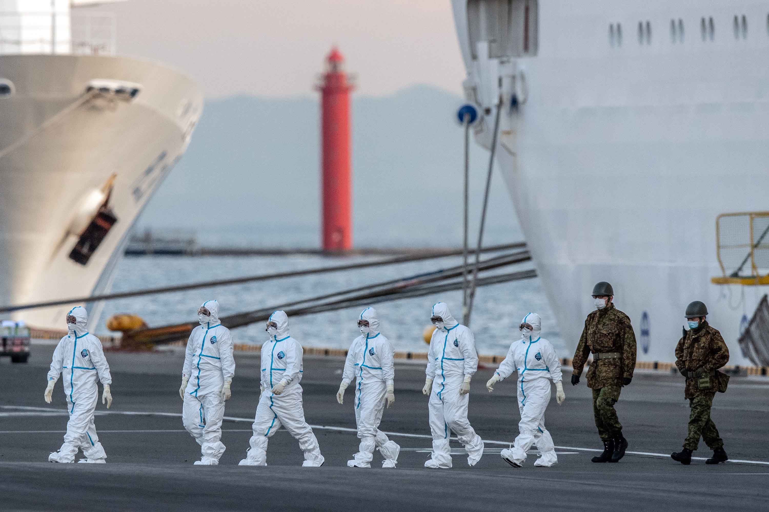 Japanese officials walk from the Diamond Princess cruise ship at Daikoku Pier in Yokohama on Monday.