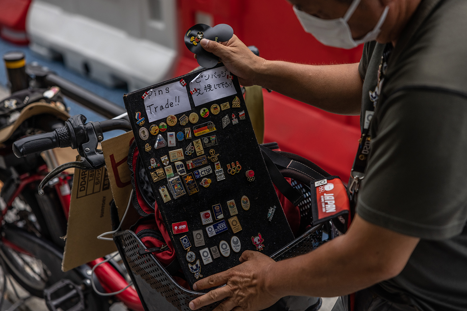 An Olympic pin collector waits to exchange pins with other collectors near the Olympic Stadium on July 29, in Tokyo.