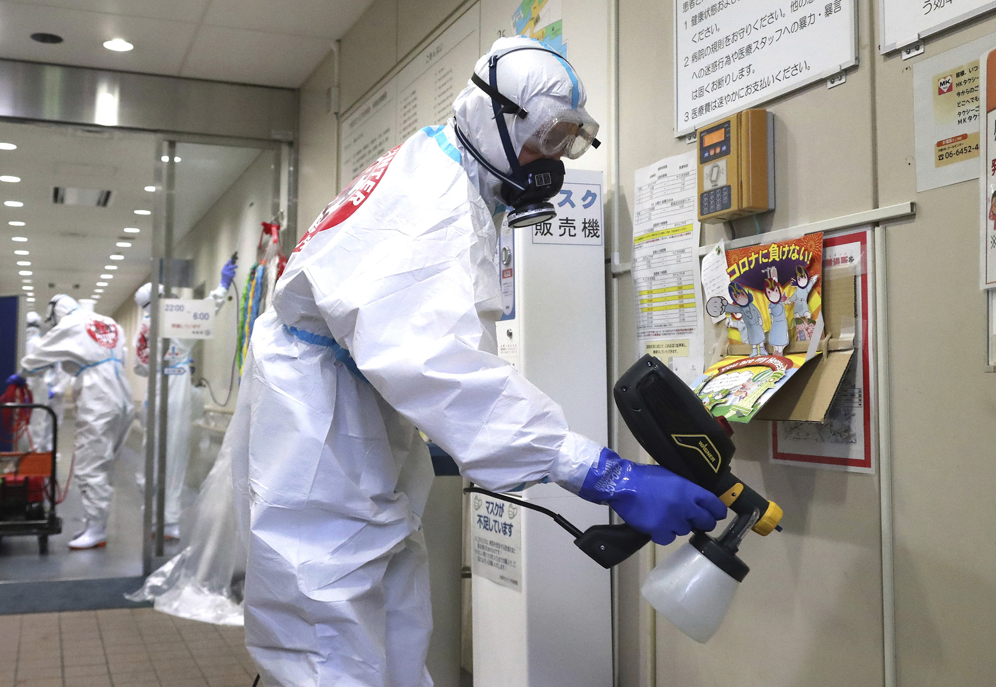 Workers disinfect inside of Osaka City Juso Hospital ahead of reopening of outpatient care in Osaka, Japan, on July 9.