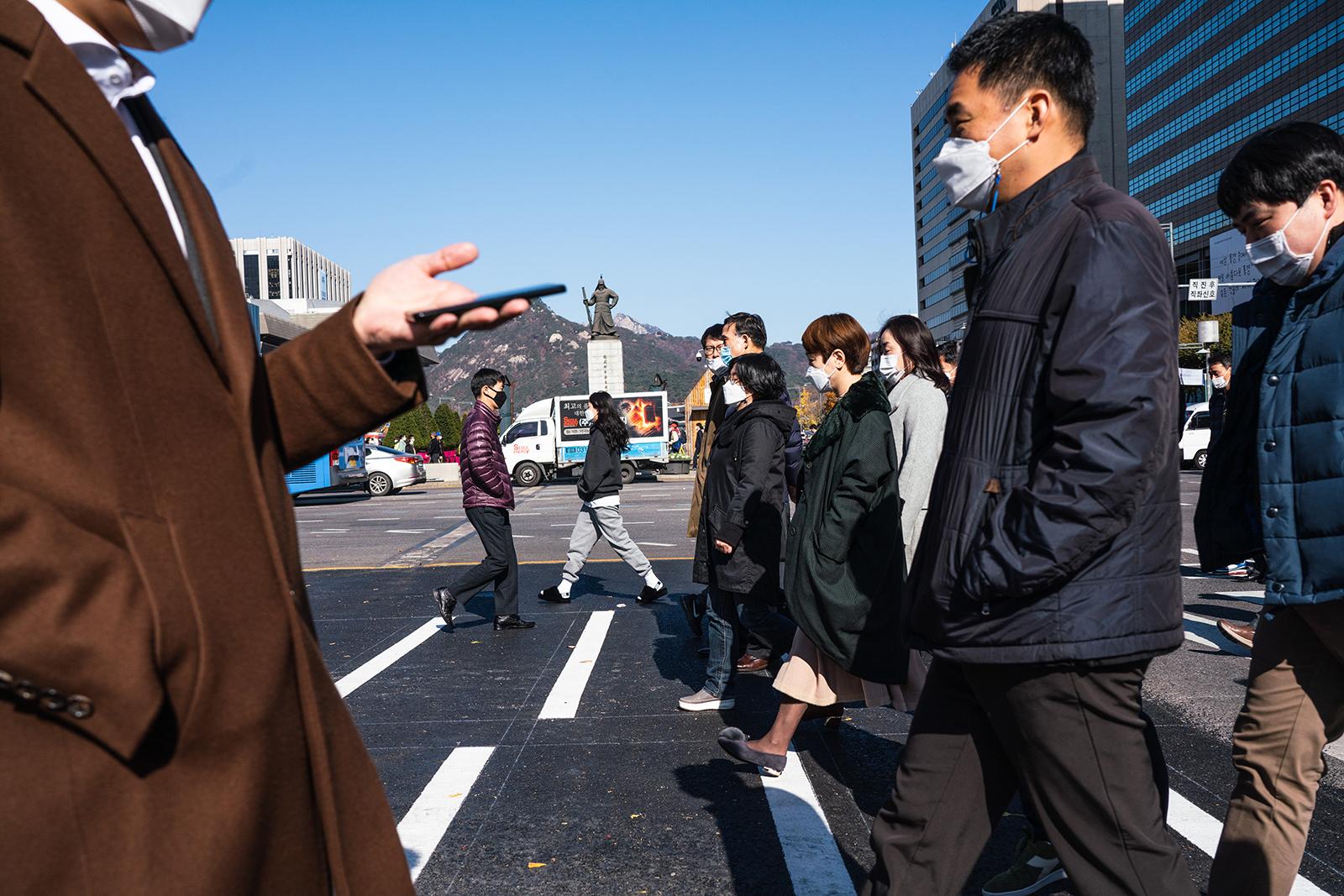 People wearing protective masks as preventative measures against coronavirus cross the road in Seoul, South Korea, on November 10.
