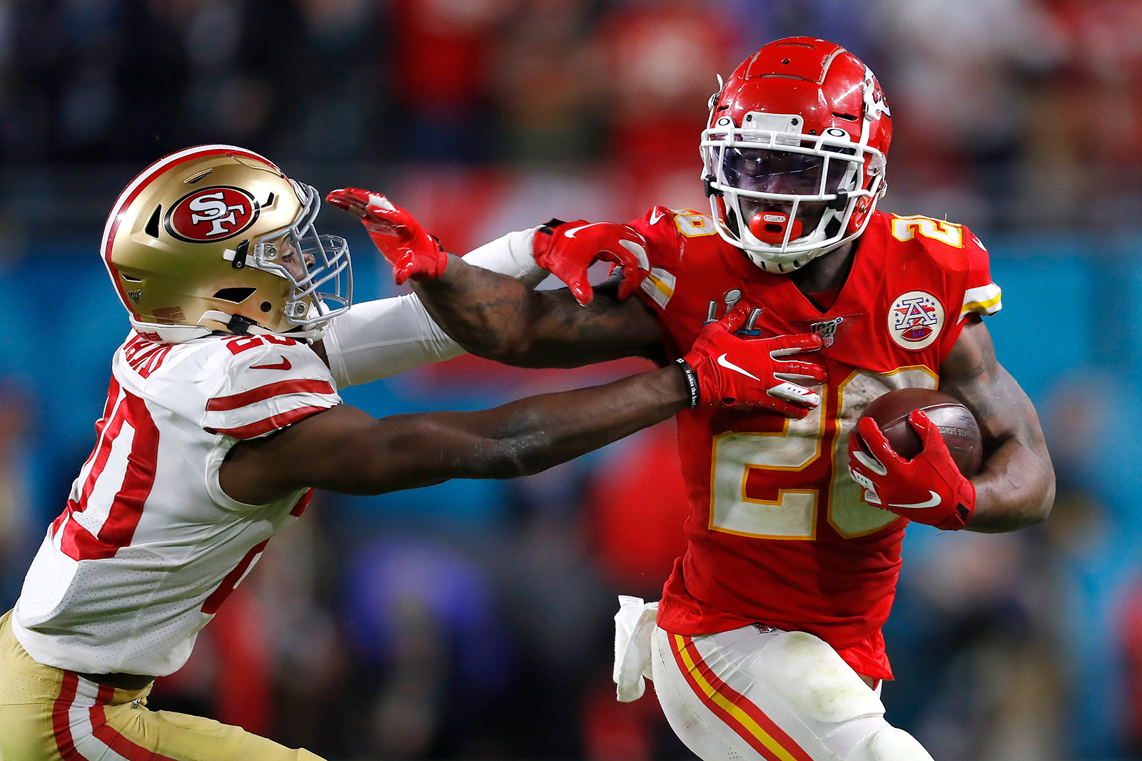 Damien Williams #26 of the Kansas City Chiefs gives a stiff arm to #20 of the San Francisco 49ers during the fourth quarter in Super Bowl LIV at Hard Rock Stadium on February 2, in Miami, Florida.