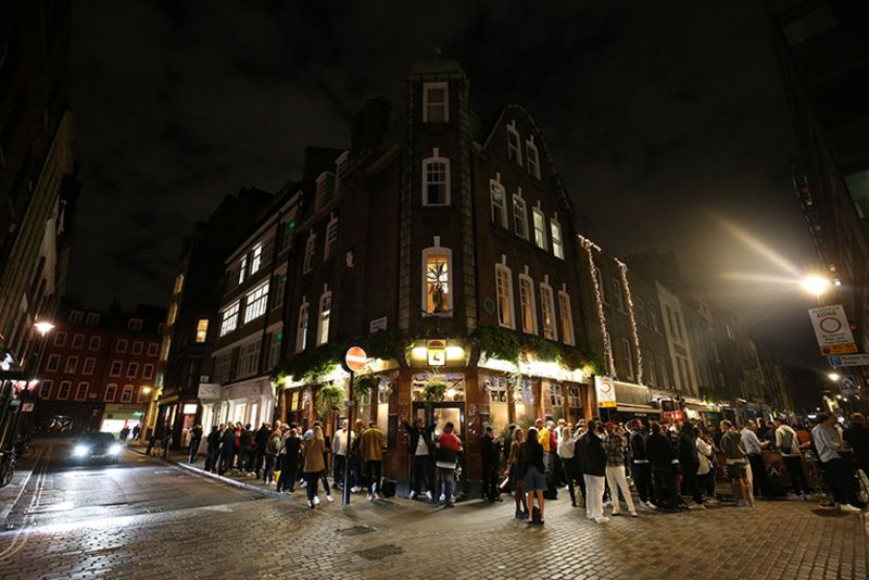 People gather outside a pub in Soho, London on September 10.