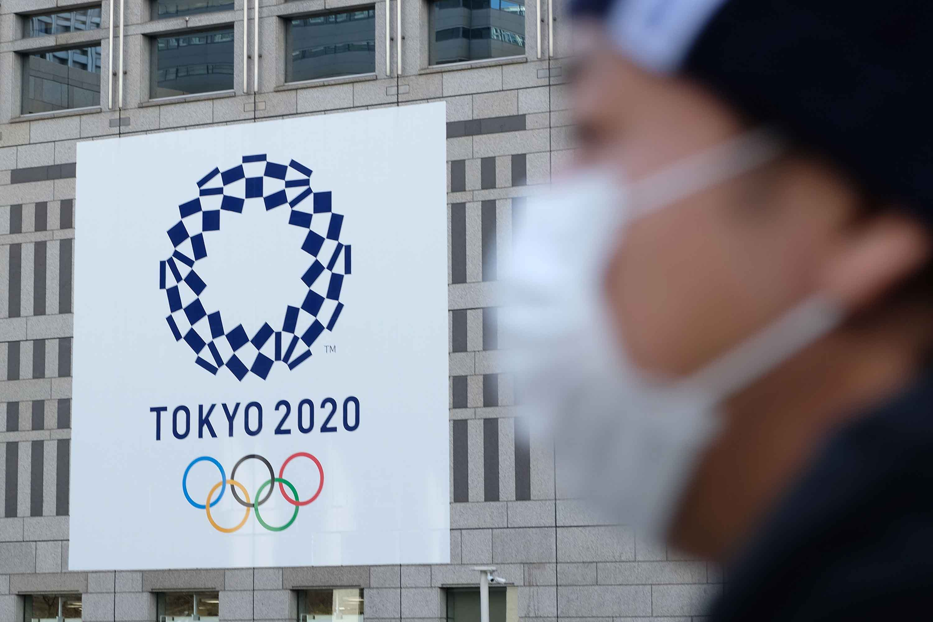 A man wearing a mask passes the logo of the Tokyo 2020 Olympic Games displayed on the Tokyo Metropolitan Government building on March 19, in Tokyo, Japan.