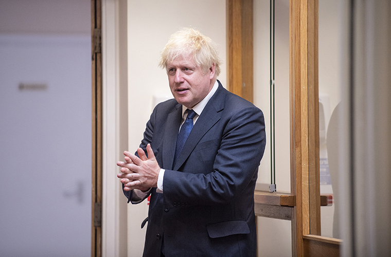 Britain's Prime Minister Boris Johnson sanitizes his hands during a visit to St Joseph's Catholic Primary School in London on Monday Aug. 10, 2020.