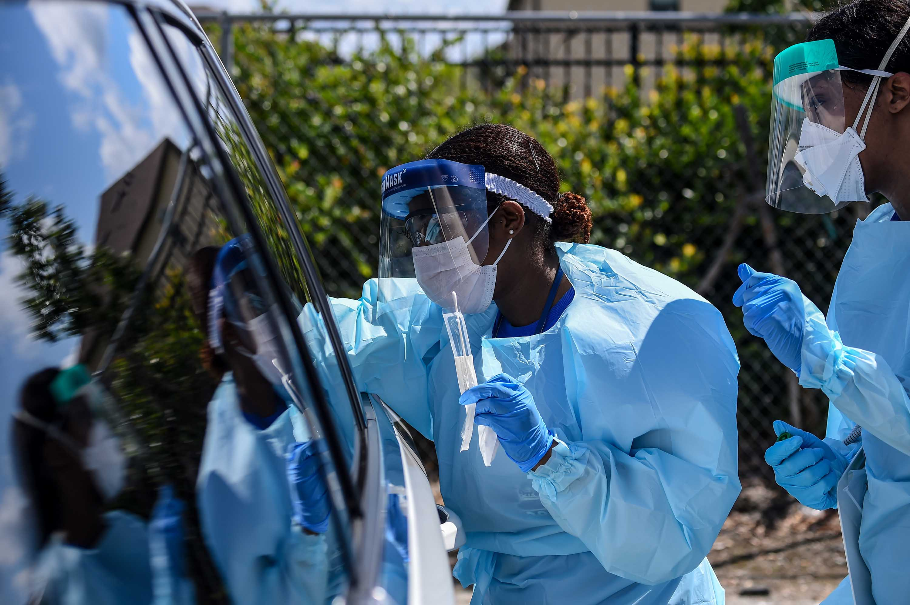 "Medical personnel take samples at a ""drive-thru"" coronavirus testing lab in West Palm Beach, Florida, on March 16."