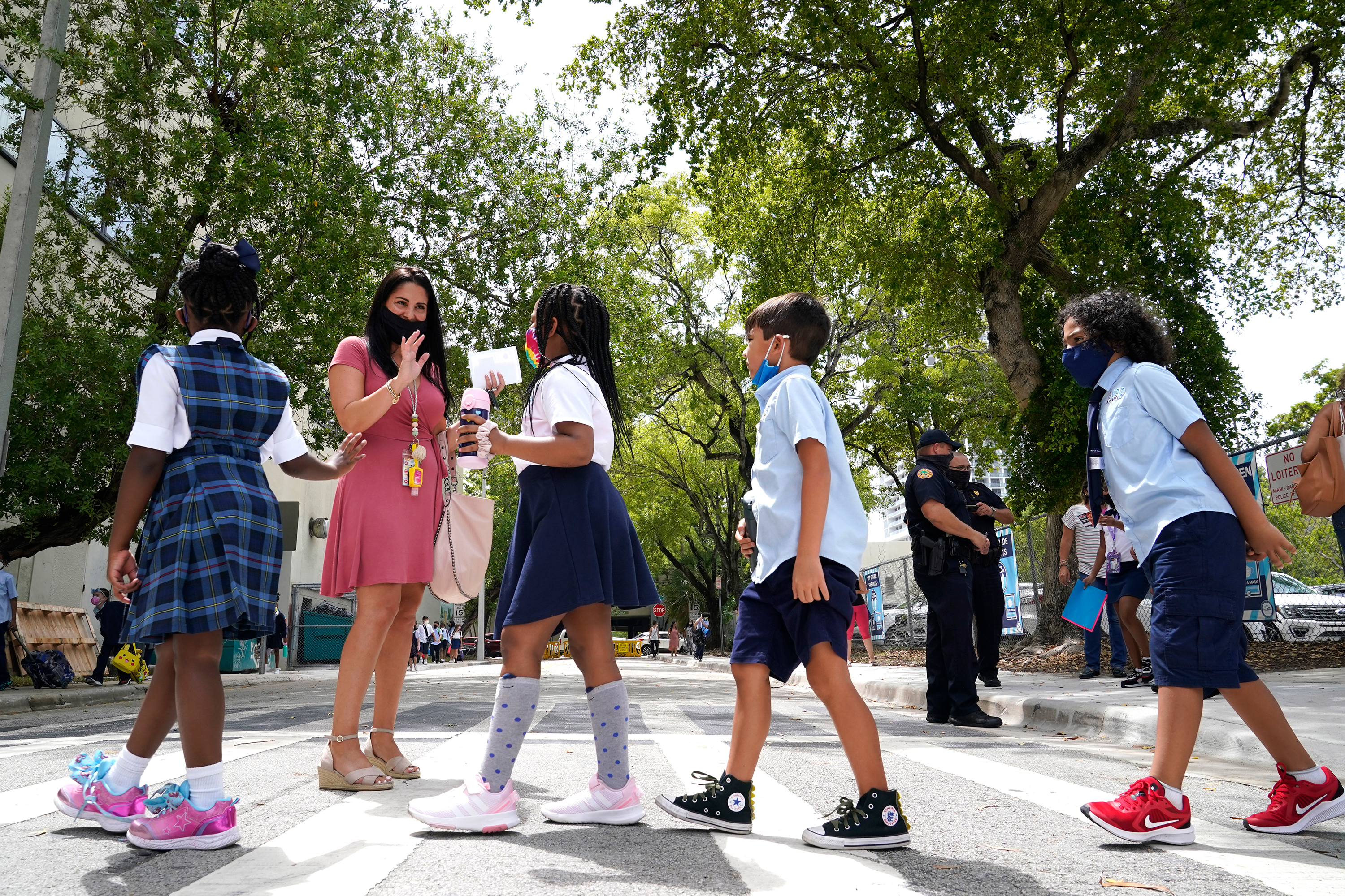 A teacher greets students outside iPrep Academy in Miami, Florida, on August 23.
