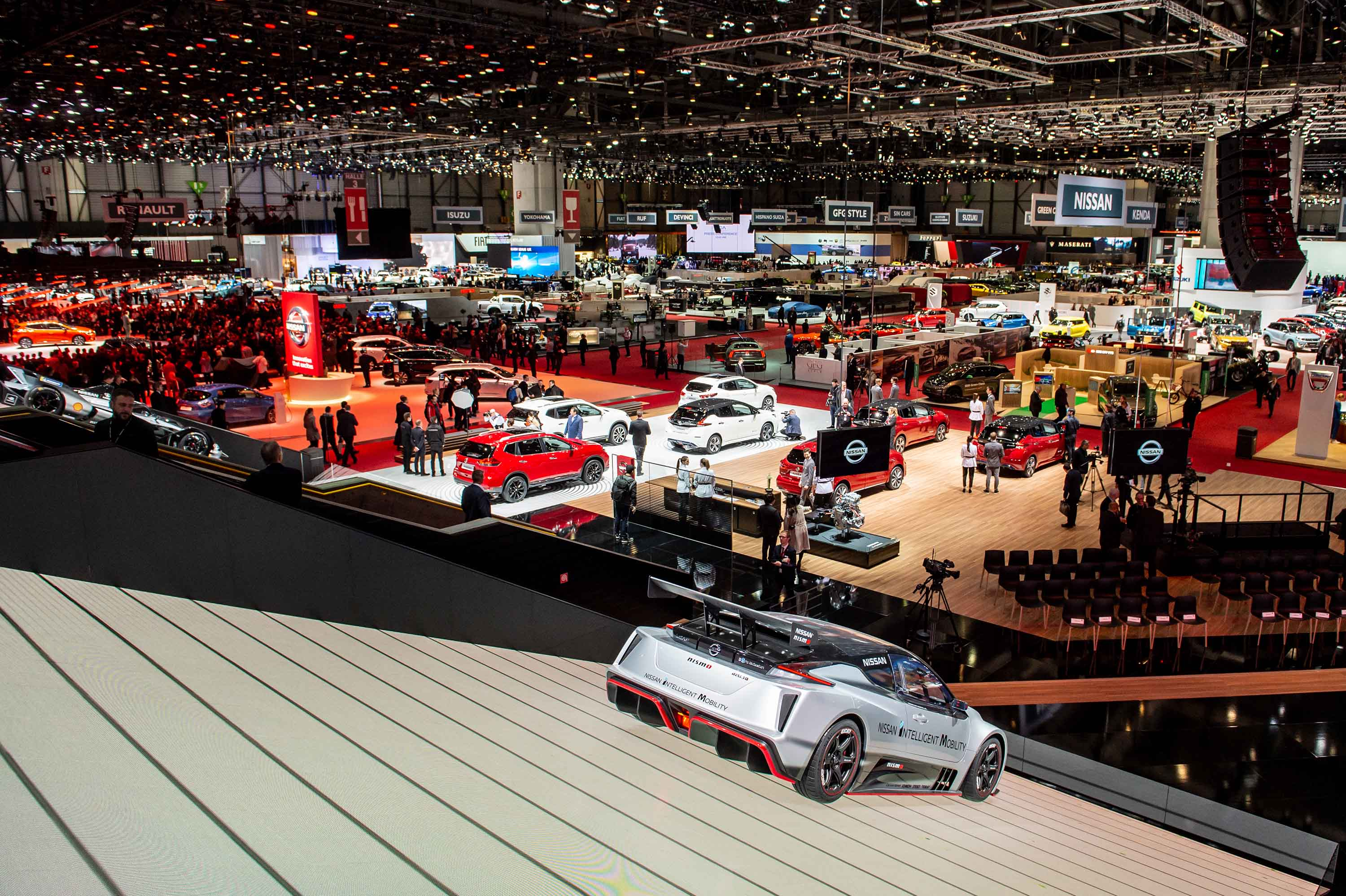 A view looking out over one section of the car show. There is another massive room full of exhibits behind the photographer.