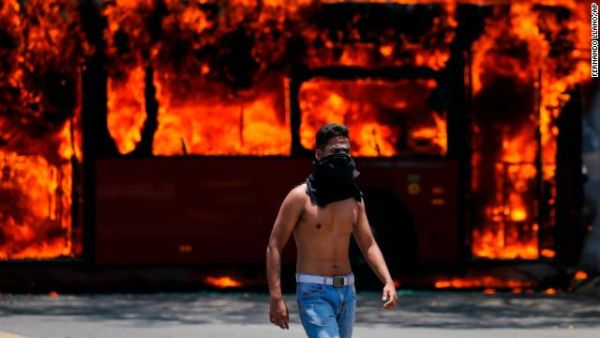 An anti-government protester walks near a bus that was set on fire by opponents of Venezuela's President Nicolás Maduro during clashes between rebel and loyalist soldiers in Caracas, Venezuela, Tuesday.