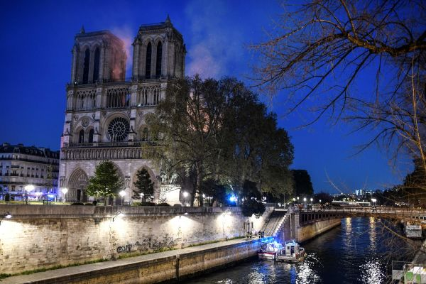Firefighters work from a quay of the River Seine at the base of Notre Dame.