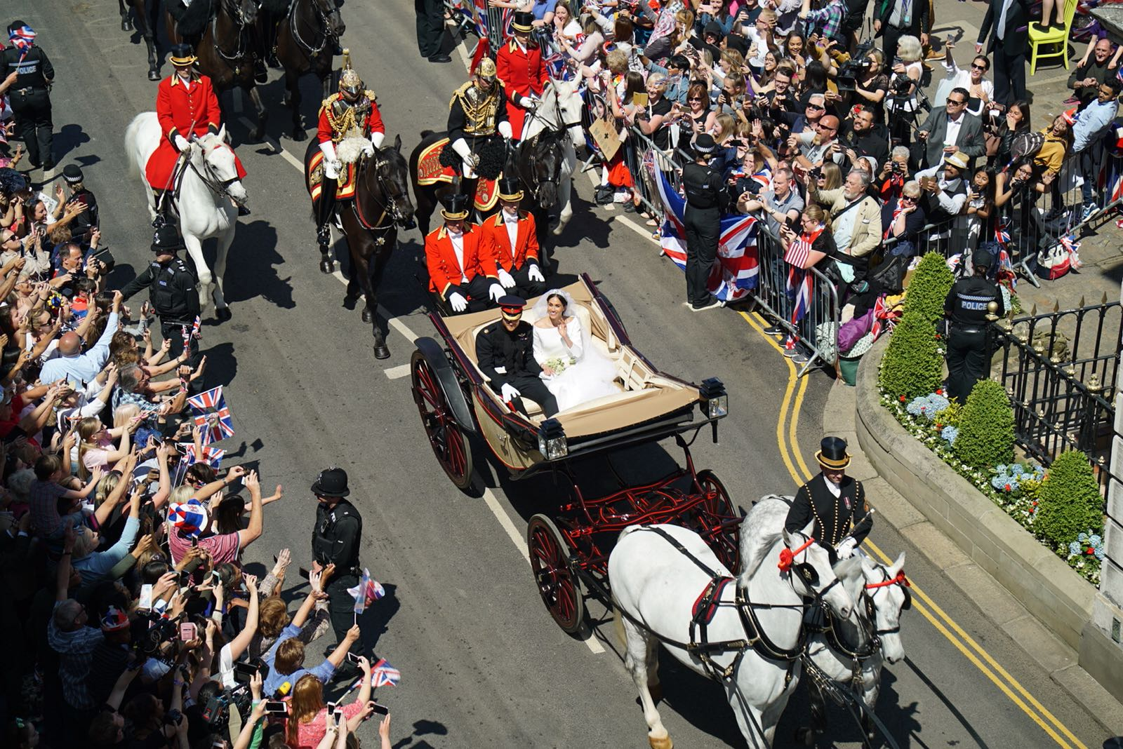 The Duke and Duchess of Sussex wave to the waiting crowds as they depart Windsor Castle.
