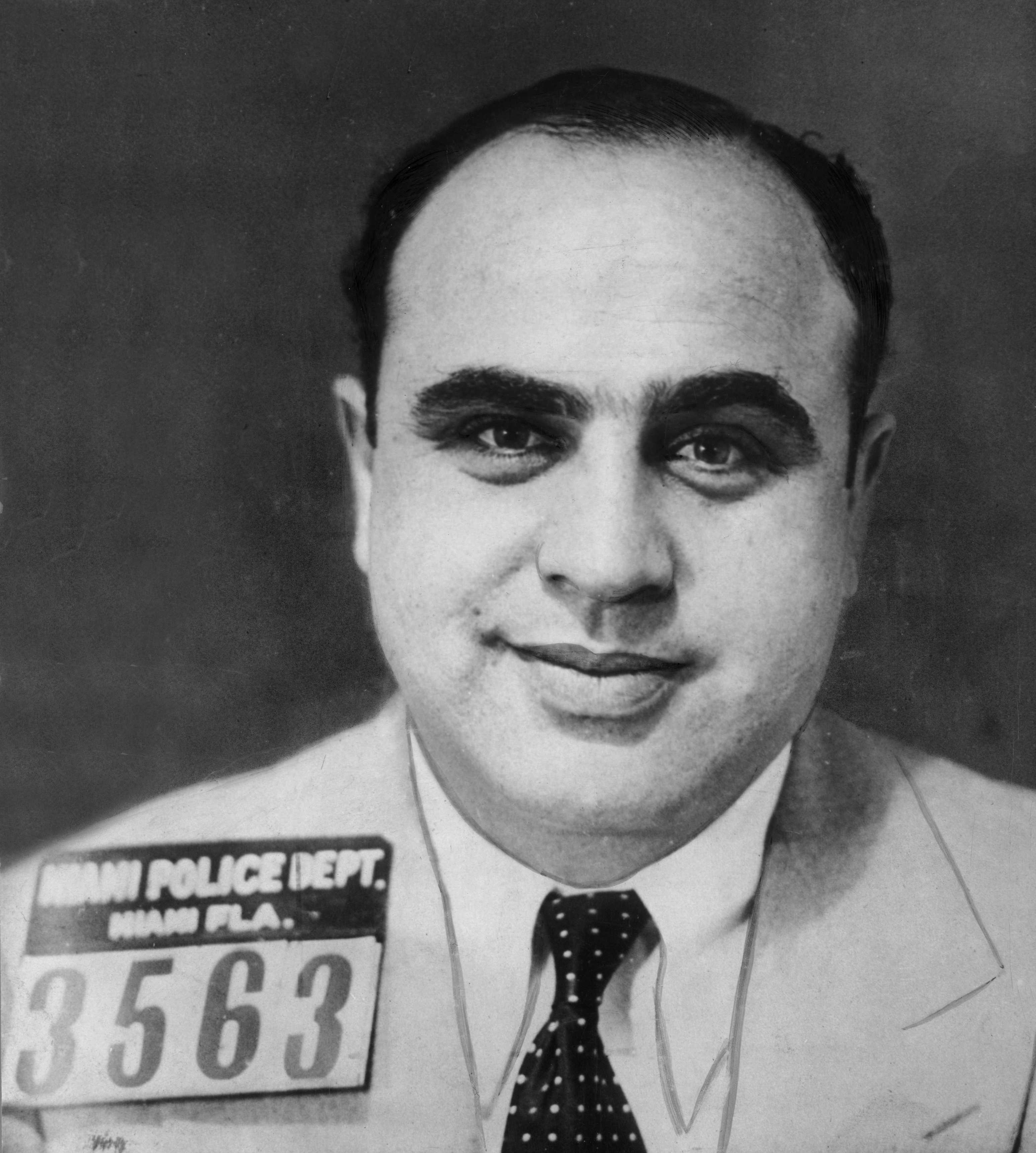 American gangster Al Capone smiles for a mugshot while wearing a jacket and tie in Miami, Florida.