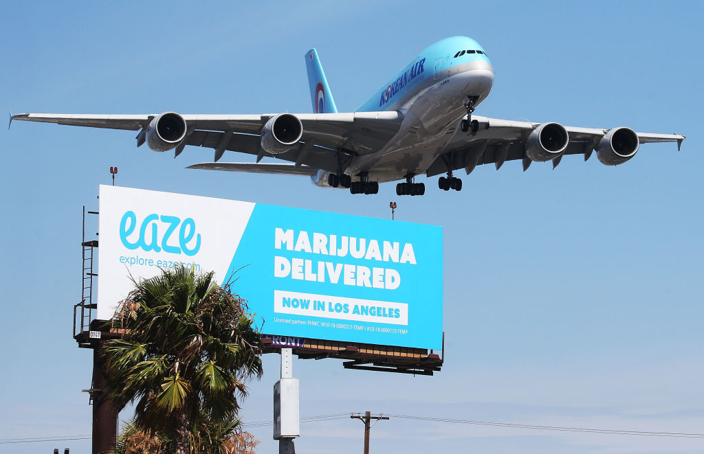 An airplane descends to land at Los Angeles International Airport above a billboard advertising the marijuana delivery service Eaze on July 12, 2018 in Los Angeles, California. A number of marijuana delivery apps are available in the state. Recreational use of marijuana became legal in California on Jan. 1.