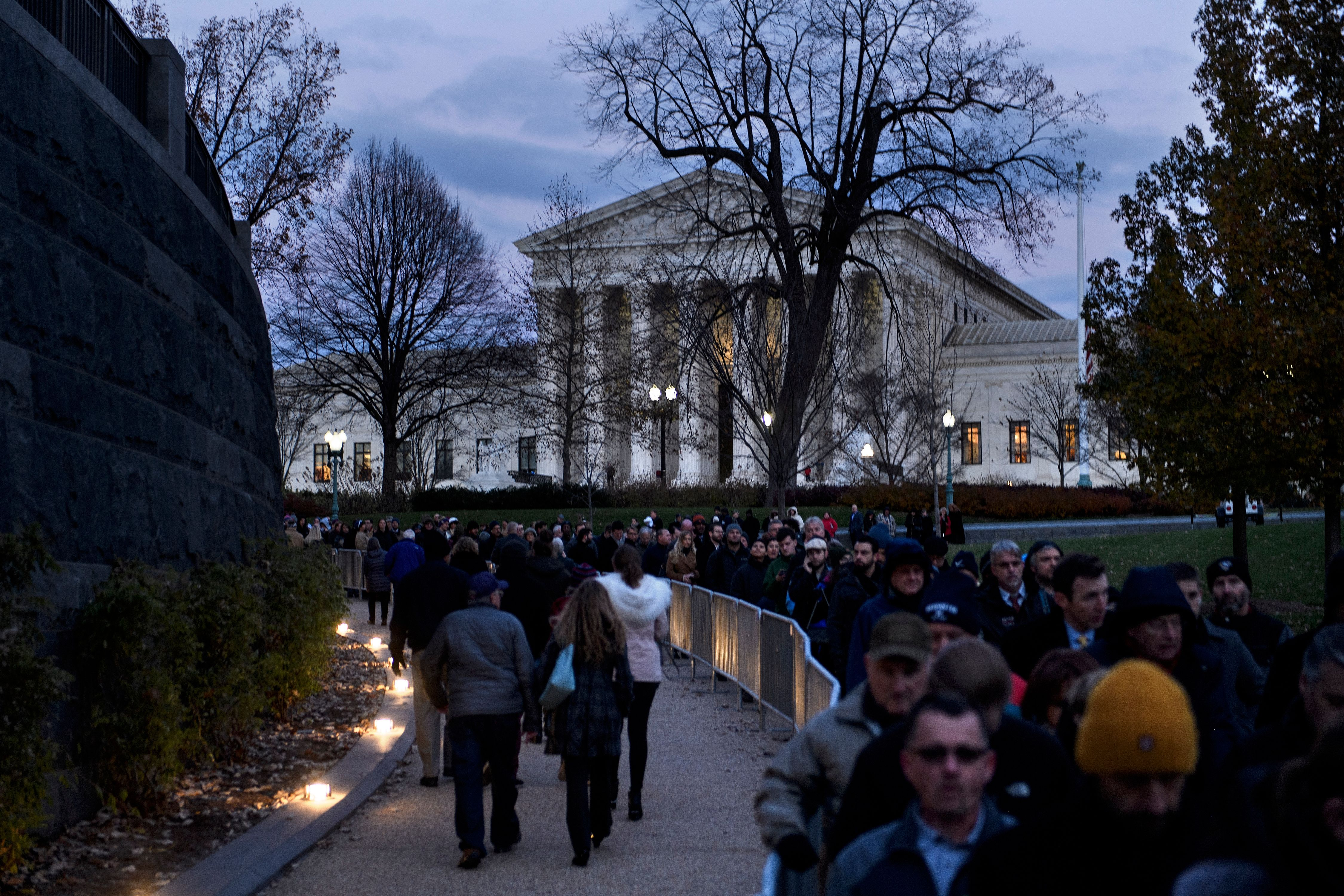 People wait in line to pay respects as the remains of former President George H.W. Bush lie in state in the US Capitol's rotunda Tuesday.