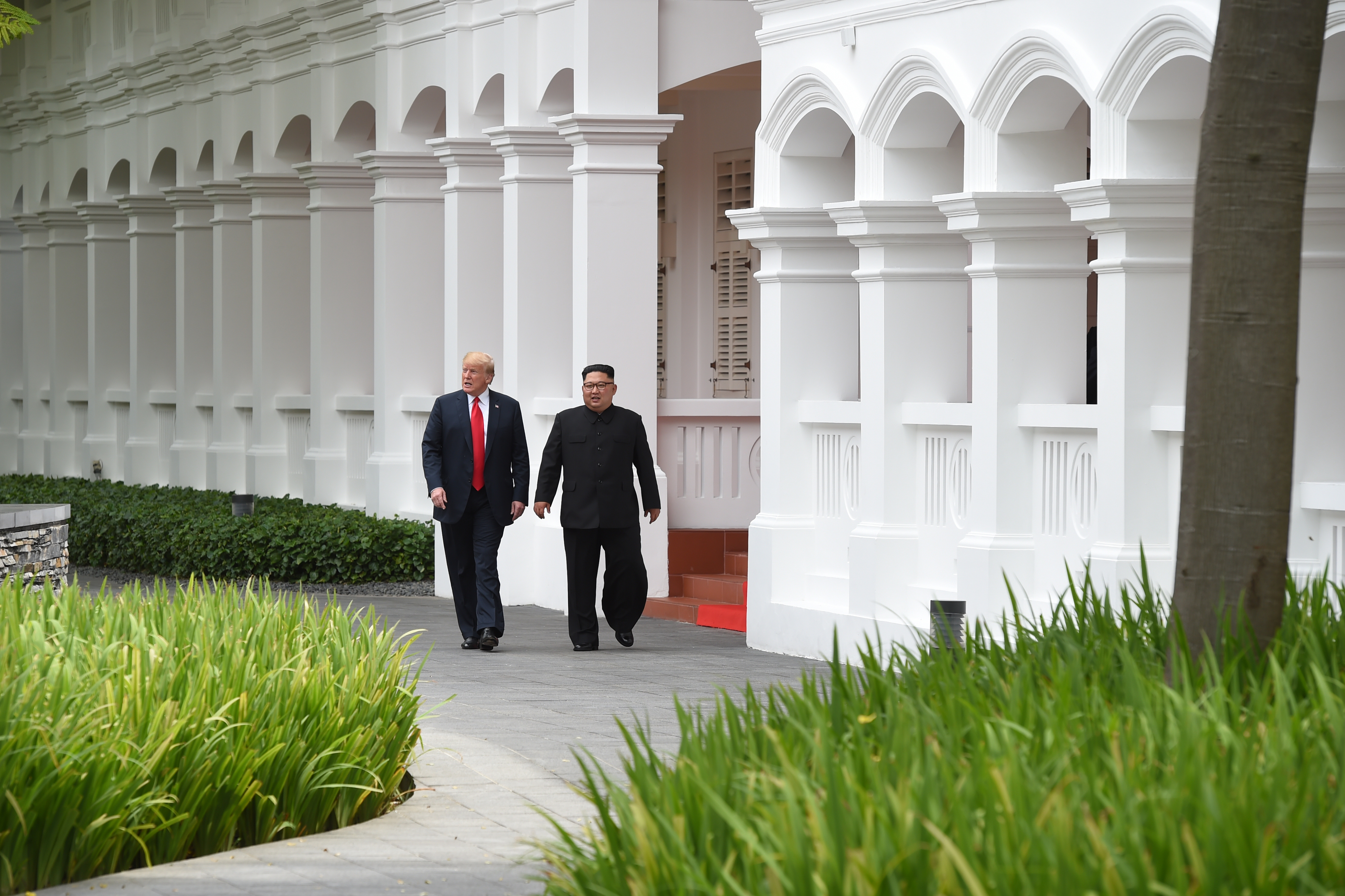 North Korea's leader Kim Jong Un (R) walks with US President Donald Trump (L) during a break in talks on June 12.