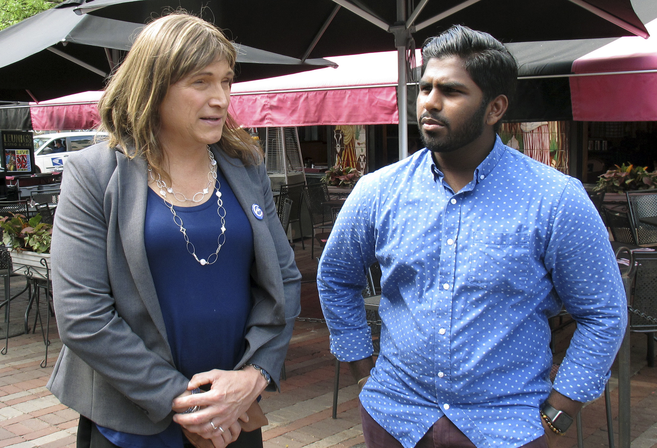 In this Aug. 9, 2018 photo, Christine Hallquist, left, transgender candidate seeking the Democratic party nomination to run for governor of Vermont, speaks with supporter Asfar Basha in Burlington, Vermont.