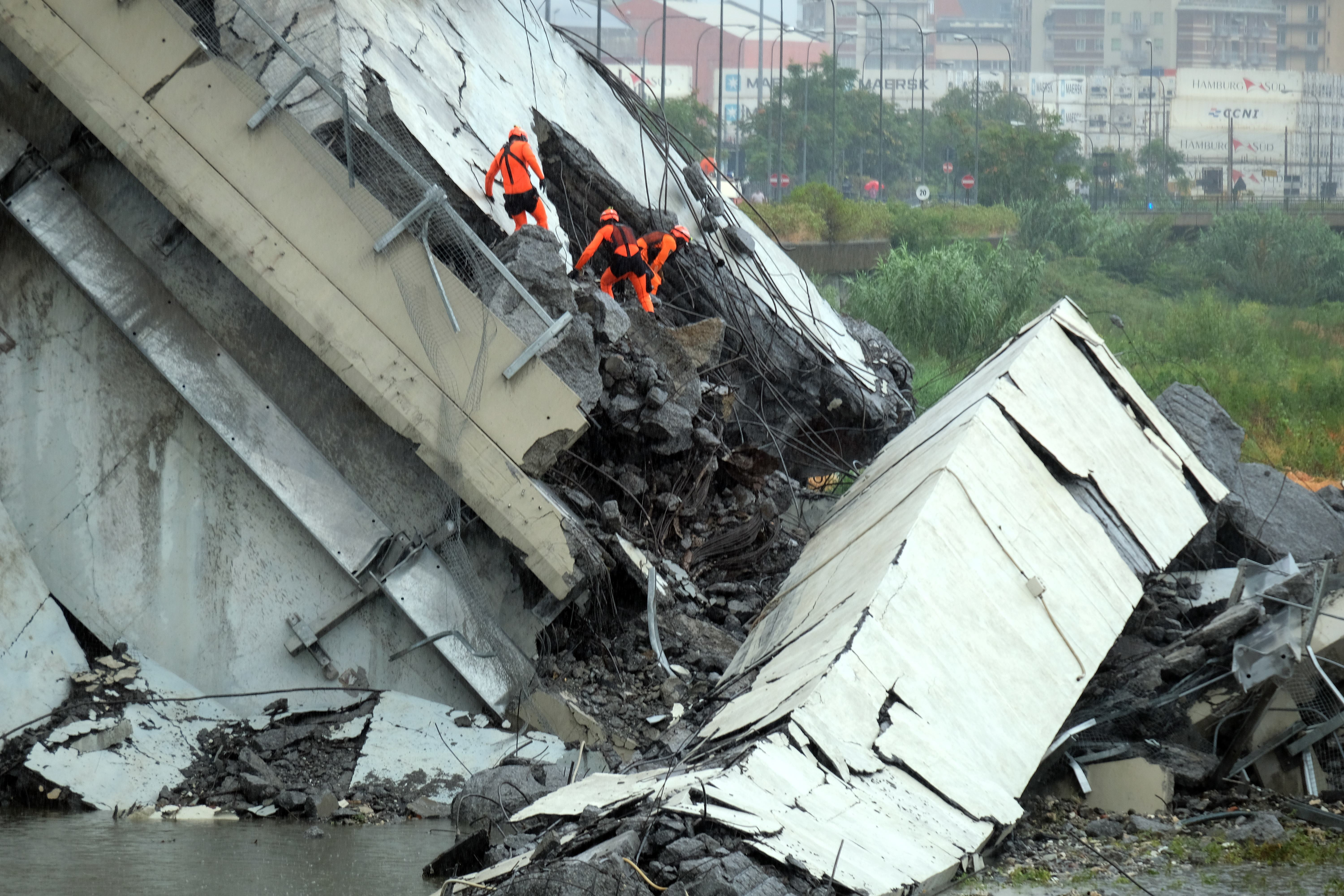 Rescuers are at work amid the rubble of a section of a giant motorway bridge that collapsed in Genoa.