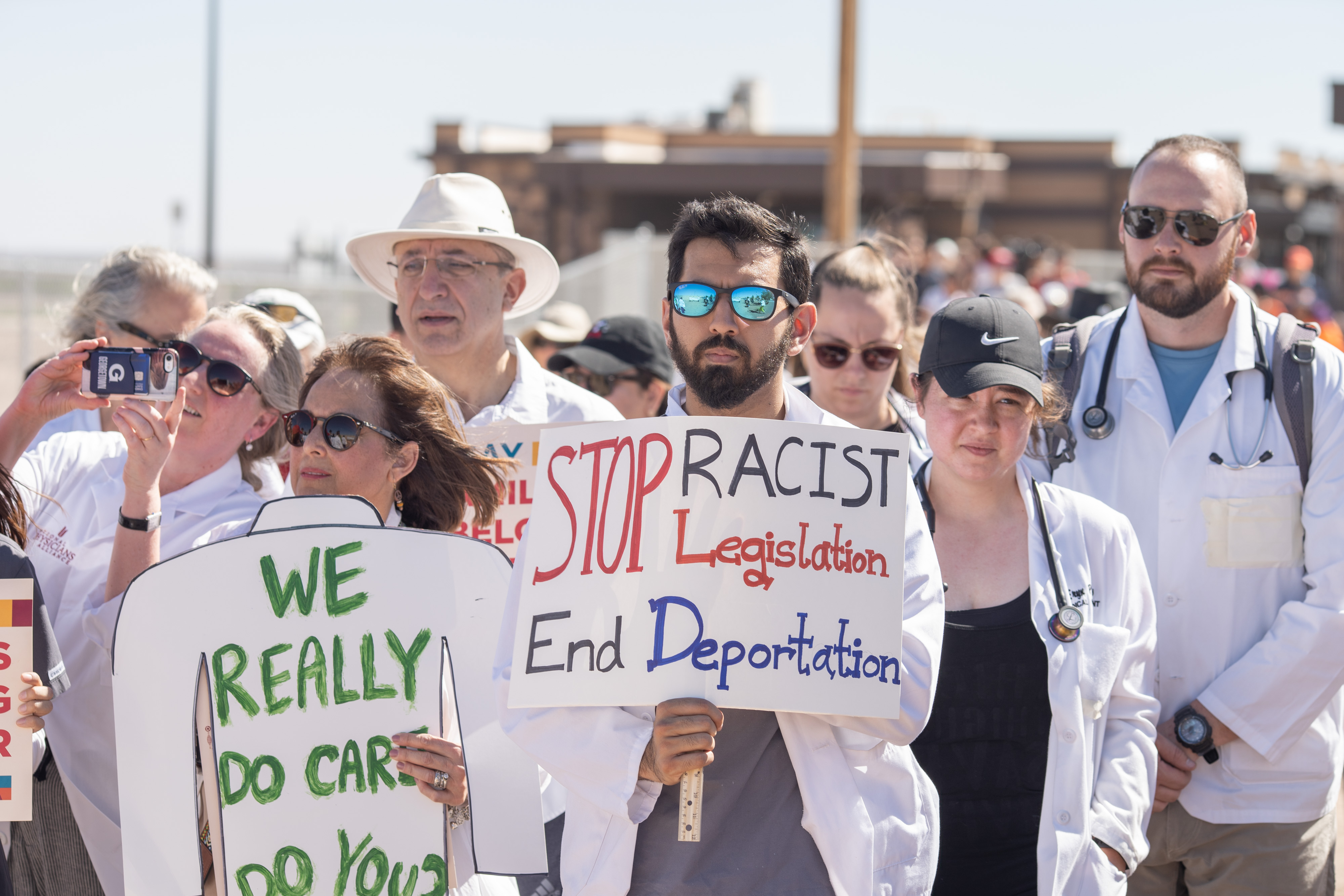 Doctors, nurses, medical students hold up posters Saturday at the Tornillo Port of Entry in Tornillo, Texas