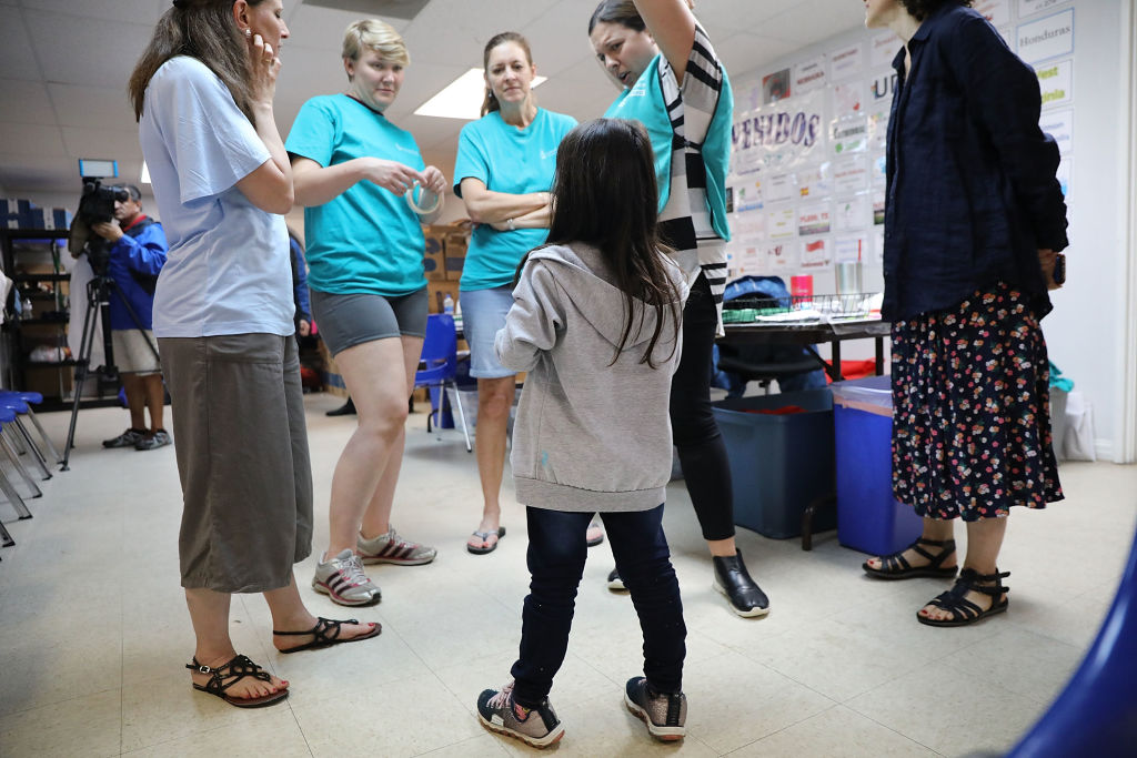 Jenquel, who recently crossed the U.S., Mexico border with her mother and siblings, speaks with volunteers at the Catholic Charities Humanitarian Respite Center on June 21, 2018 in McAllen, Texas.