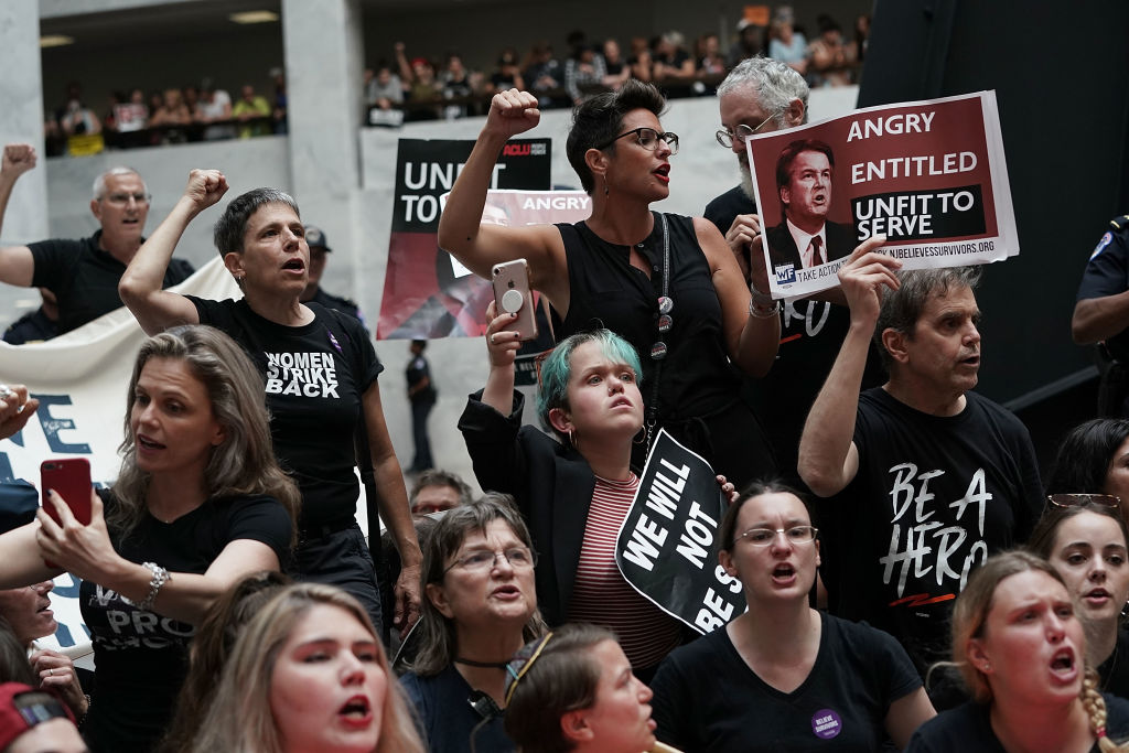 Activists shout slogans during a protest against the confirmation of Supreme Court nominee Judge Brett Kavanaugh October 4, 2018 at the Hart Senate Office Building on Capitol Hill in Washington, DC.