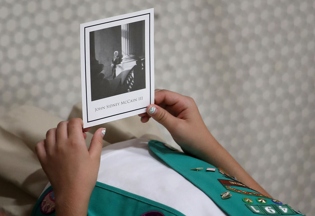 A Girl Scout holds a picture of the late Sen. John McCain as his body lies in state at the Arizona Capitol in Phoenix.