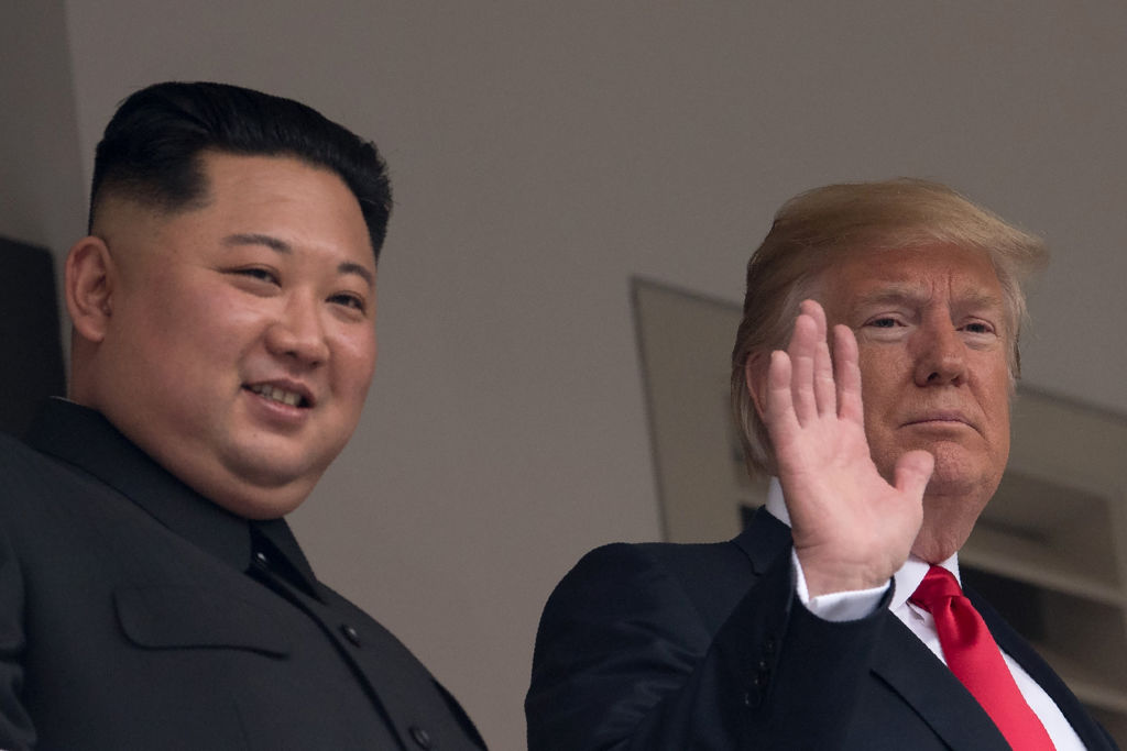 US President Donald Trump waves as he and North Korea's leader Kim Jong Un look on from a veranda during their historic US-North Korea summit, at the Capella Hotel on Sentosa island in Singapore on June 12, 2018.