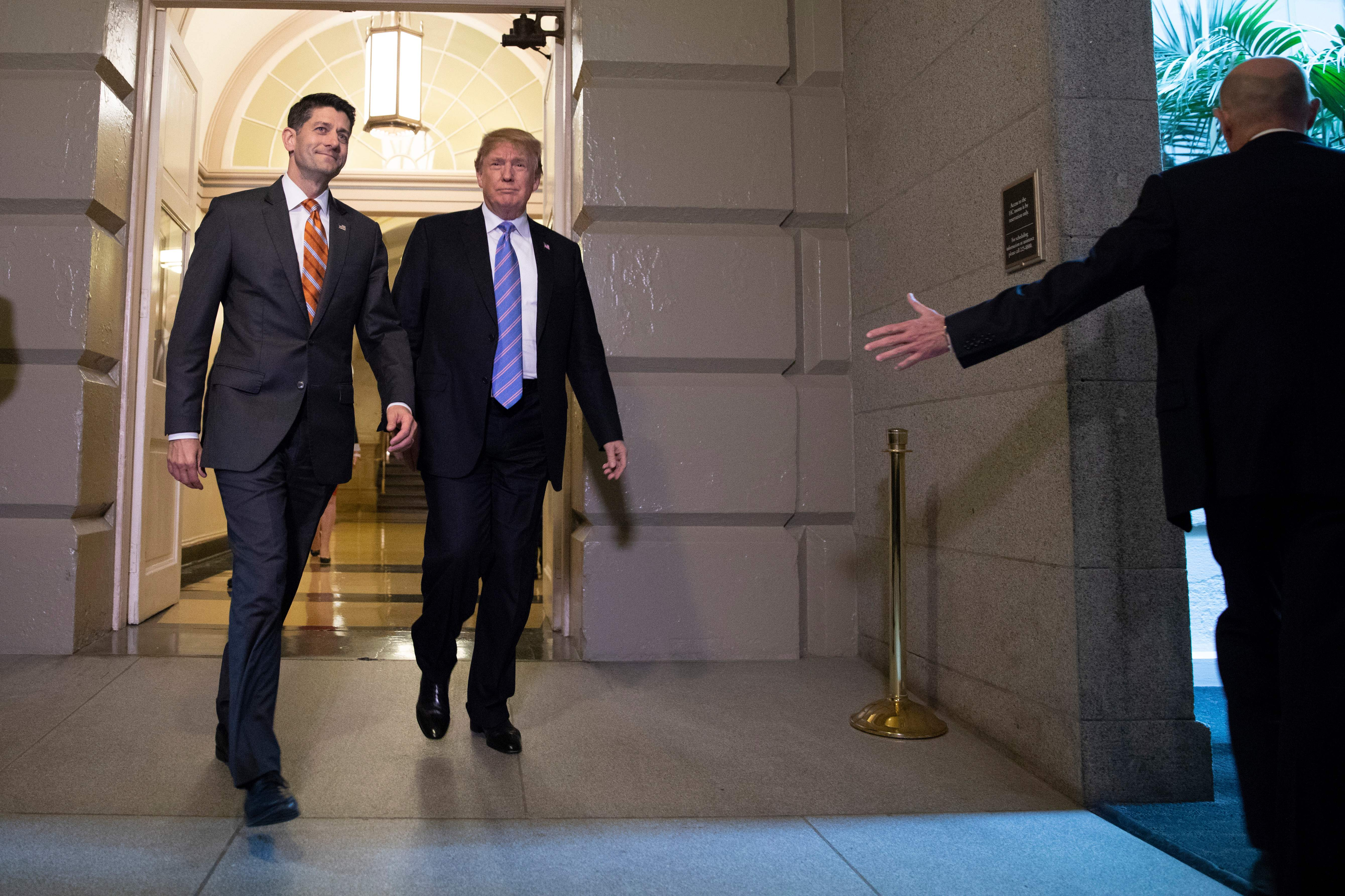Trump, accompanied by House Speaker Paul Ryan, arrive for a meeting with Republican members of Congress on Tuesday.