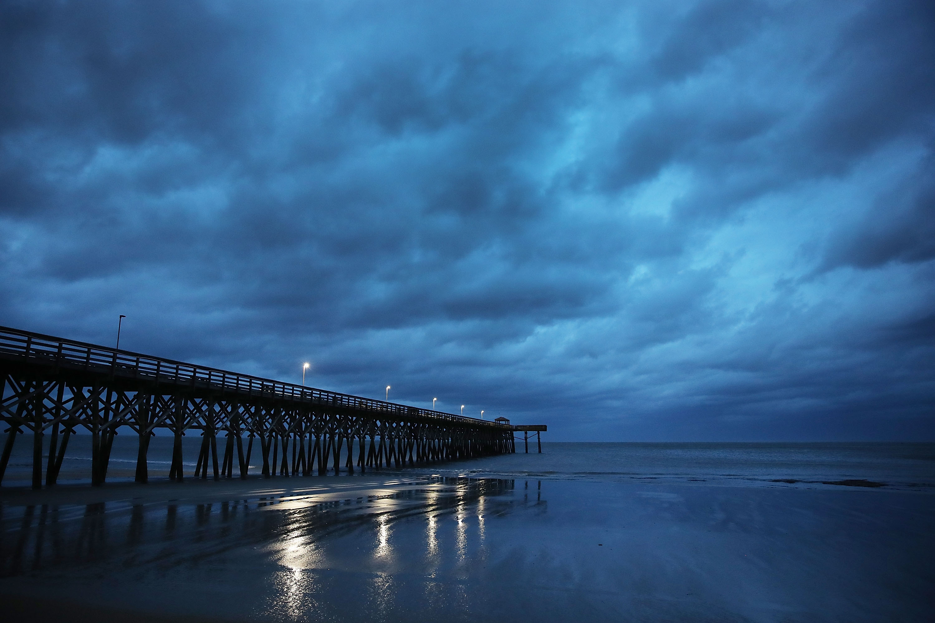 Storm clouds are seen over a pier in Myrtle Beach on Friday