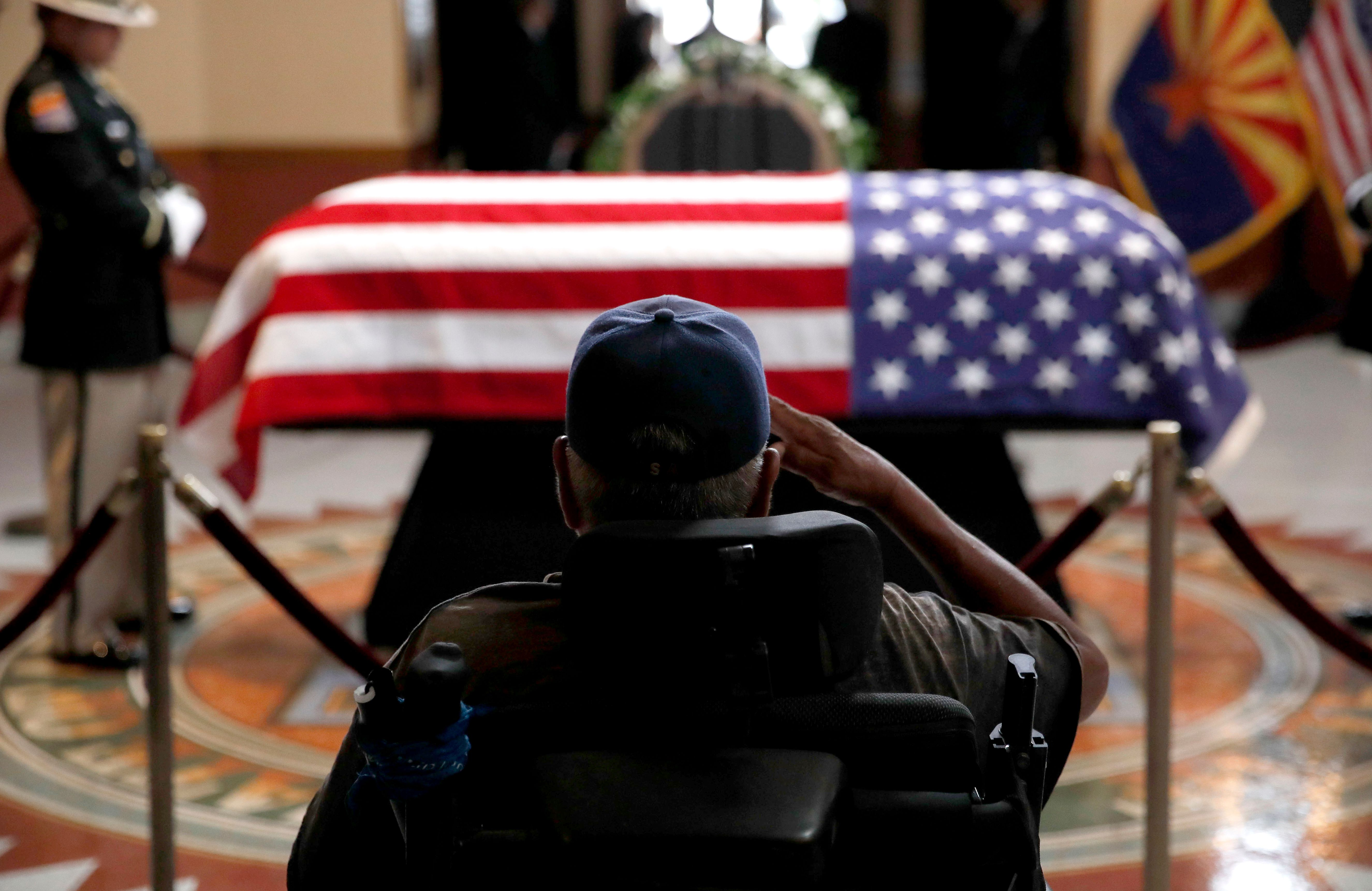 A former serviceman salutes the casket during a memorial service for US Sen. John McCain at the Arizona Capitol on Aug. 29, 2018, in Phoenix.