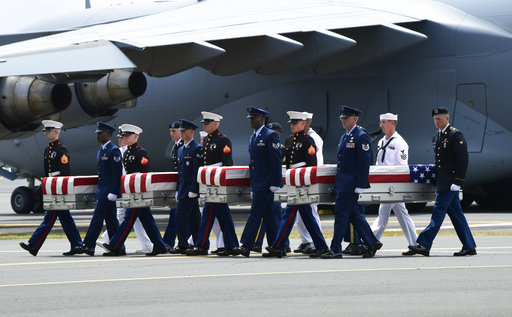 Military members carry transfer cases from a C-17 at a ceremony marking the arrival of the remains believed to be of American service members who fell in the Korean War at Joint Base Pearl Harbor-Hickam, Hawaii, on Wednesday, Aug. 1, 2018.