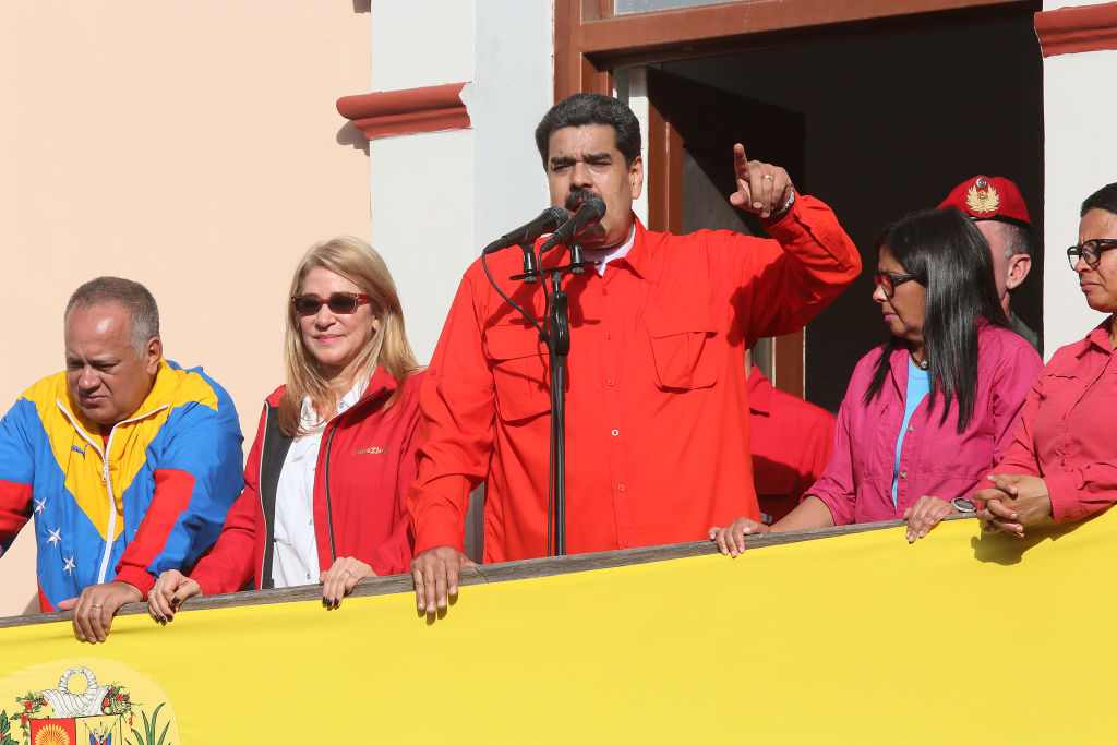 Nicolás Maduro (C) waves a national flag as he is escorted by Diosdado Cabello, president of National Constitutional Assembly; first lady Cilia Flores; executive Vice President Delcy Rodriguez and Major Erika Farias at the Balcón del Pueblo of the Miraflores Government Palace on Jan. 23, 2019 in Caracas, Venezuela.