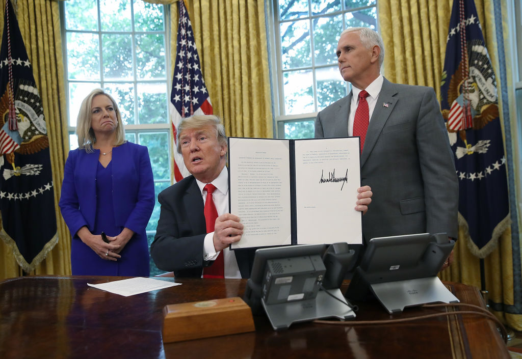 President Trump, accompanied by Department of Homeland Security Secretary Kirstjen Nielsen (L) and U.S. Vice President Mike Pence (R), displays an executive order on June 20, 2018 in Washington, DC.