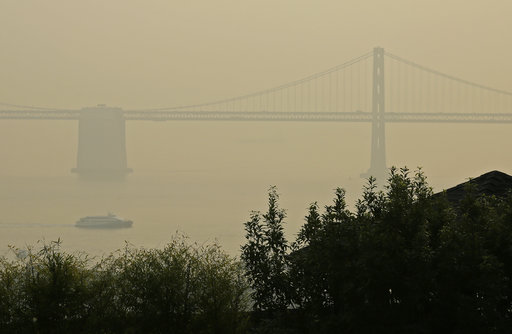A ferryboat and the San Francisco-Oakland Bay Bridge are obscured due to smoke and haze from wildfires Monday in San Francisco.