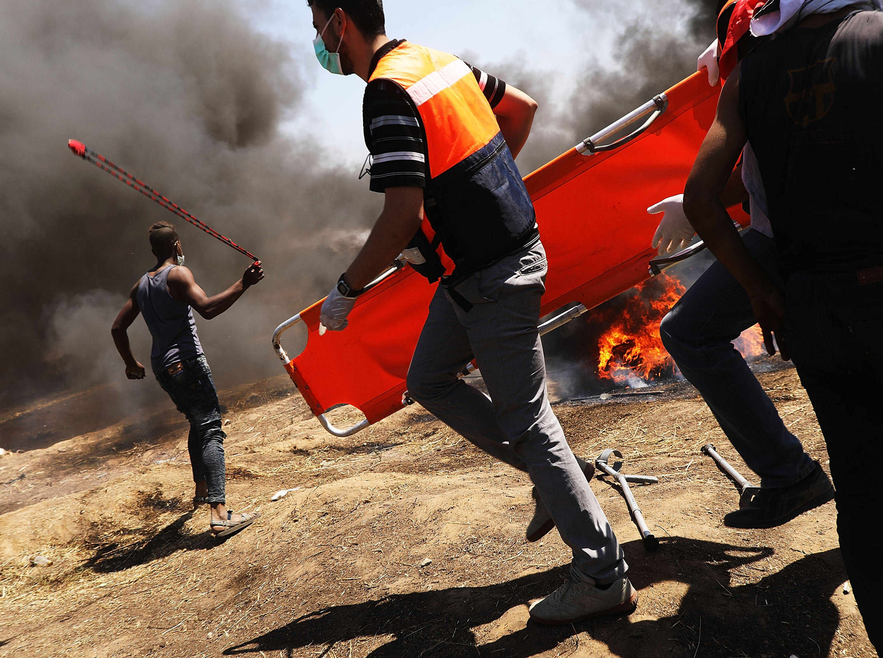 Medics rush in as Palestinians clash with Israeli soldiers at the border fence with Israel as mass demonstrations at the fence continue on May 14, 2018 in Gaza City, Gaza.