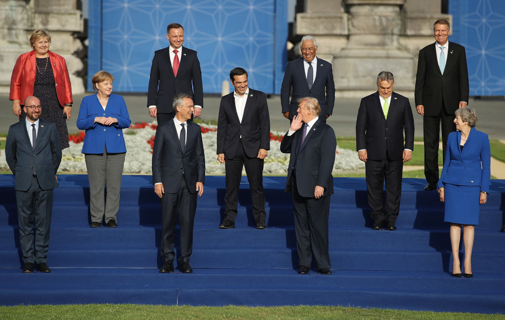 President Donald Trump holds his hand to his face as he says something to other heads of state and governments, including German Chancellor Angela Merkel, British Prime Minister Theresa May, NATO Secretary General Jens Stoltenberg and Greek Prime Minister Alexis Tsipras, gathered for a group photo at the evening reception and dinner at the 2018 NATO Summit on July 11, 2018 in Brussels, Belgium.