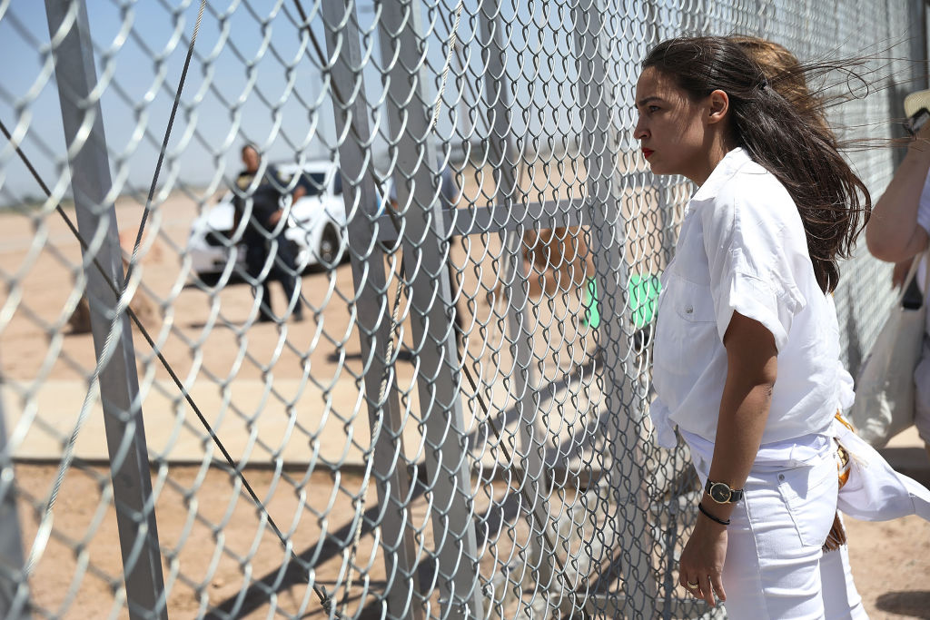 Alexandria Ocasio-Cortez stands at the Tornillo-Guadalupe port of entry gate on June 24, 2018 in Tornillo, Texas. She is part of a group protesting the separation of children from their parents after they were caught entering the U.S. under the administration's zero tolerance policy.