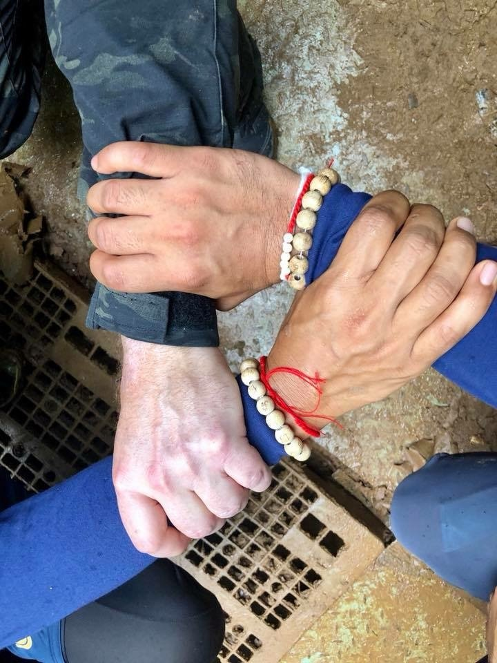 A photo posted to the Royal Thai Navy SEALs page shows three interlocked wrists.