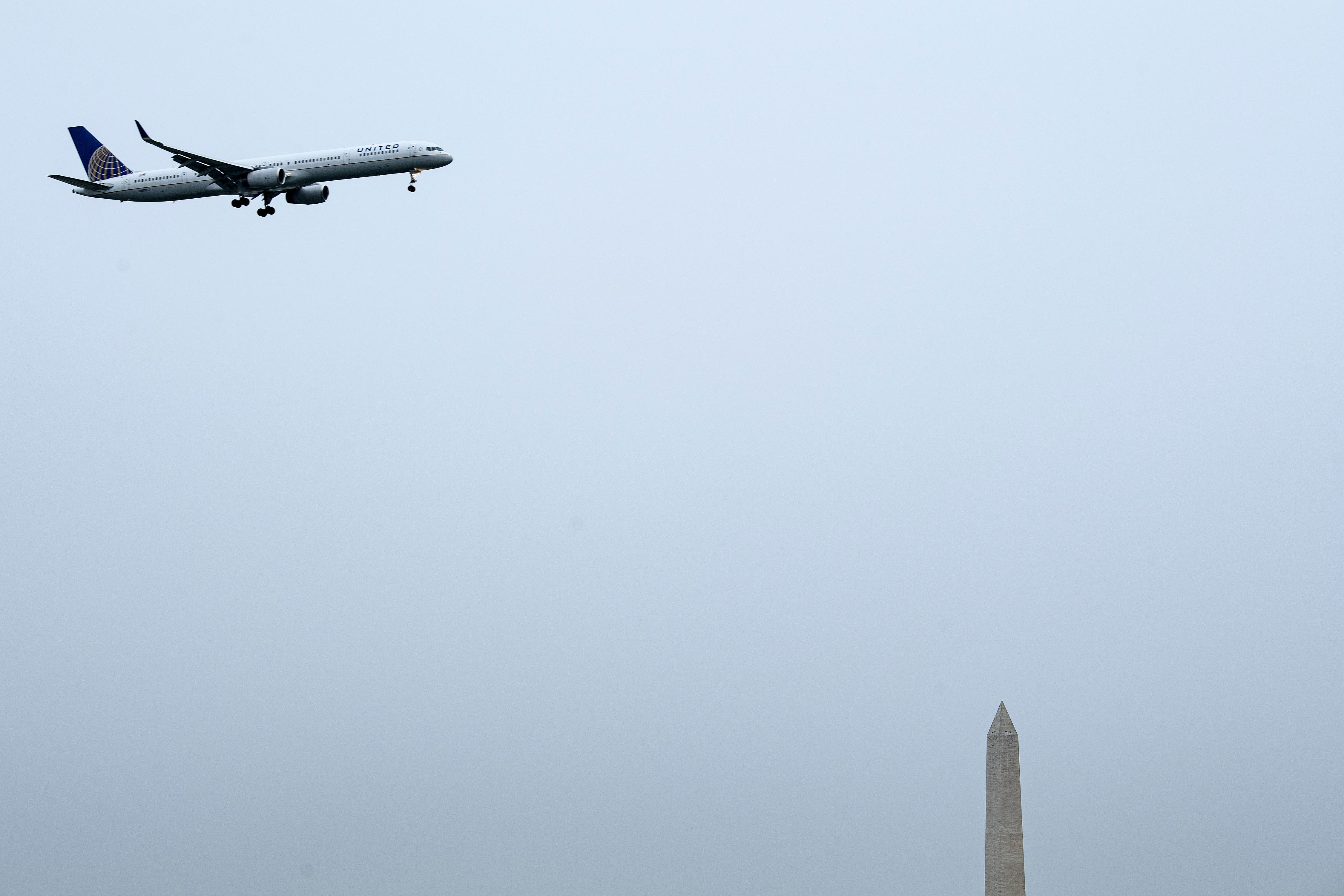 A United Airlines plane passes the Washington Monument.
