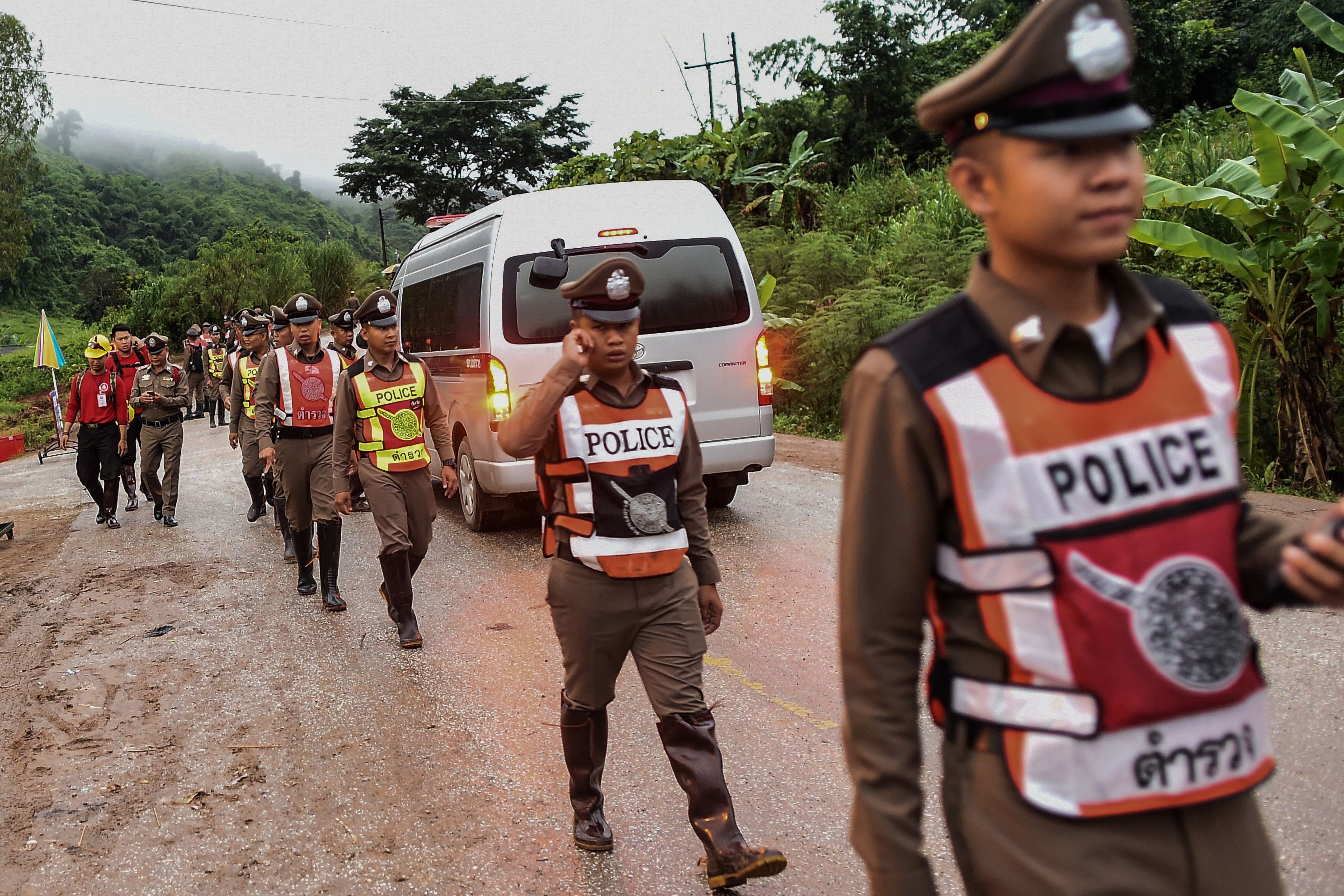 Thai policemen secure the road leading to Tham Luang cave area as rescue operations continue for those still trapped inside the cave.