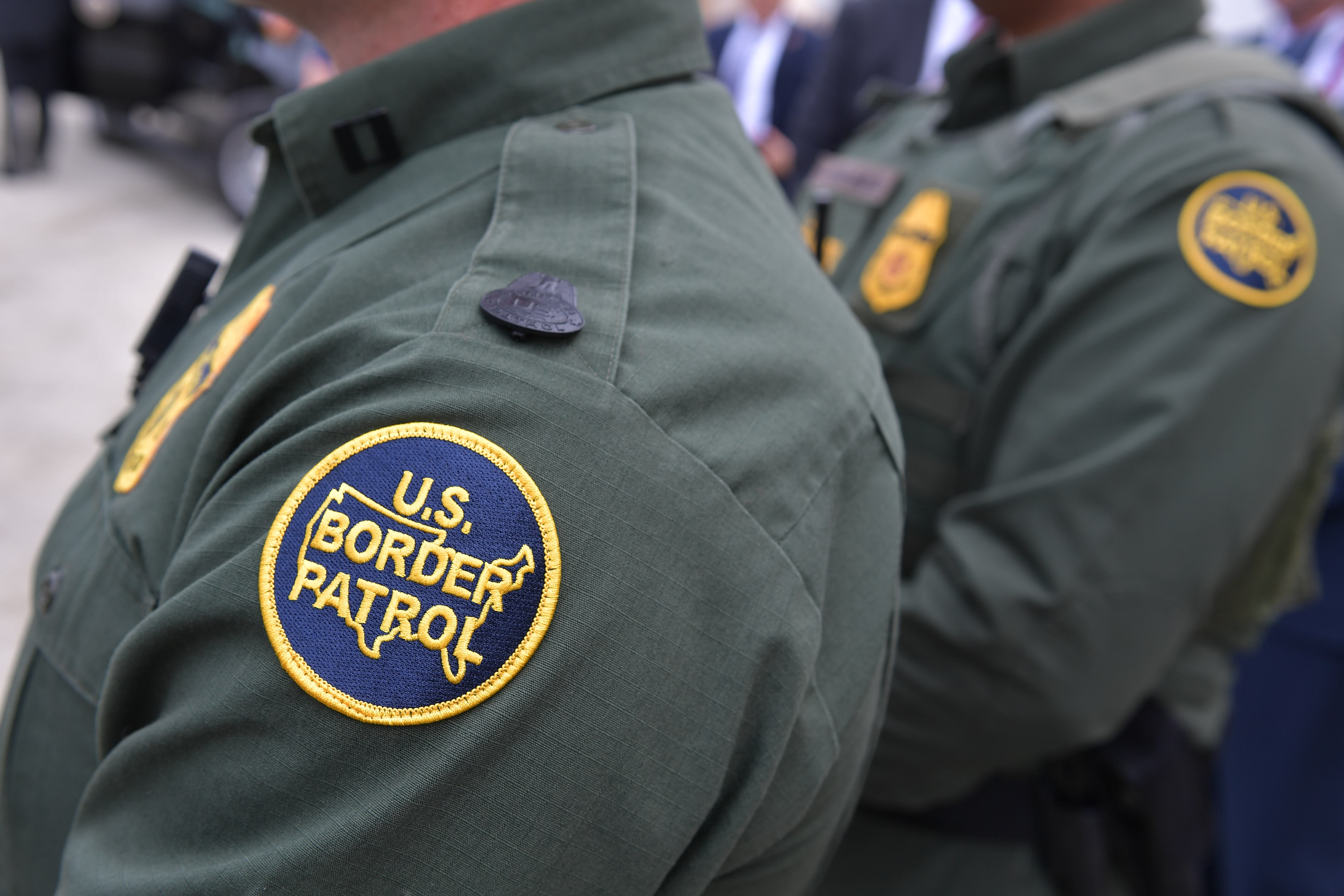 Members of the US Border Patrol listen as US President Donald Trump speaks after inspecting border wall prototypes in San Diego, California on March 13, 2018.