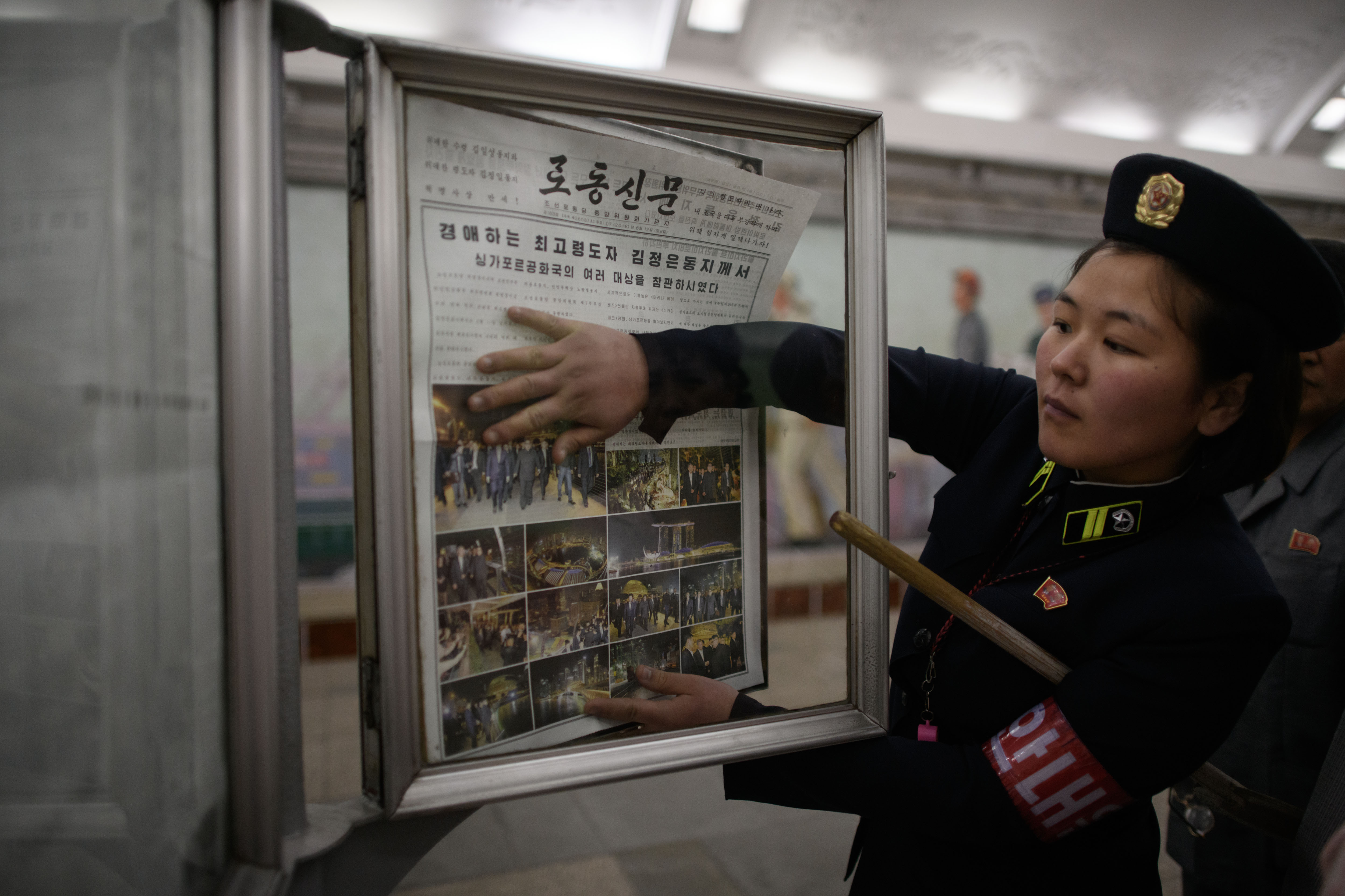 A conductor changes the newspaper to the latest edition showing images of North Korean leader Kim Jong Un in Singapore, at a news stand on a subway platform of the Pyongyang metro on June 12.