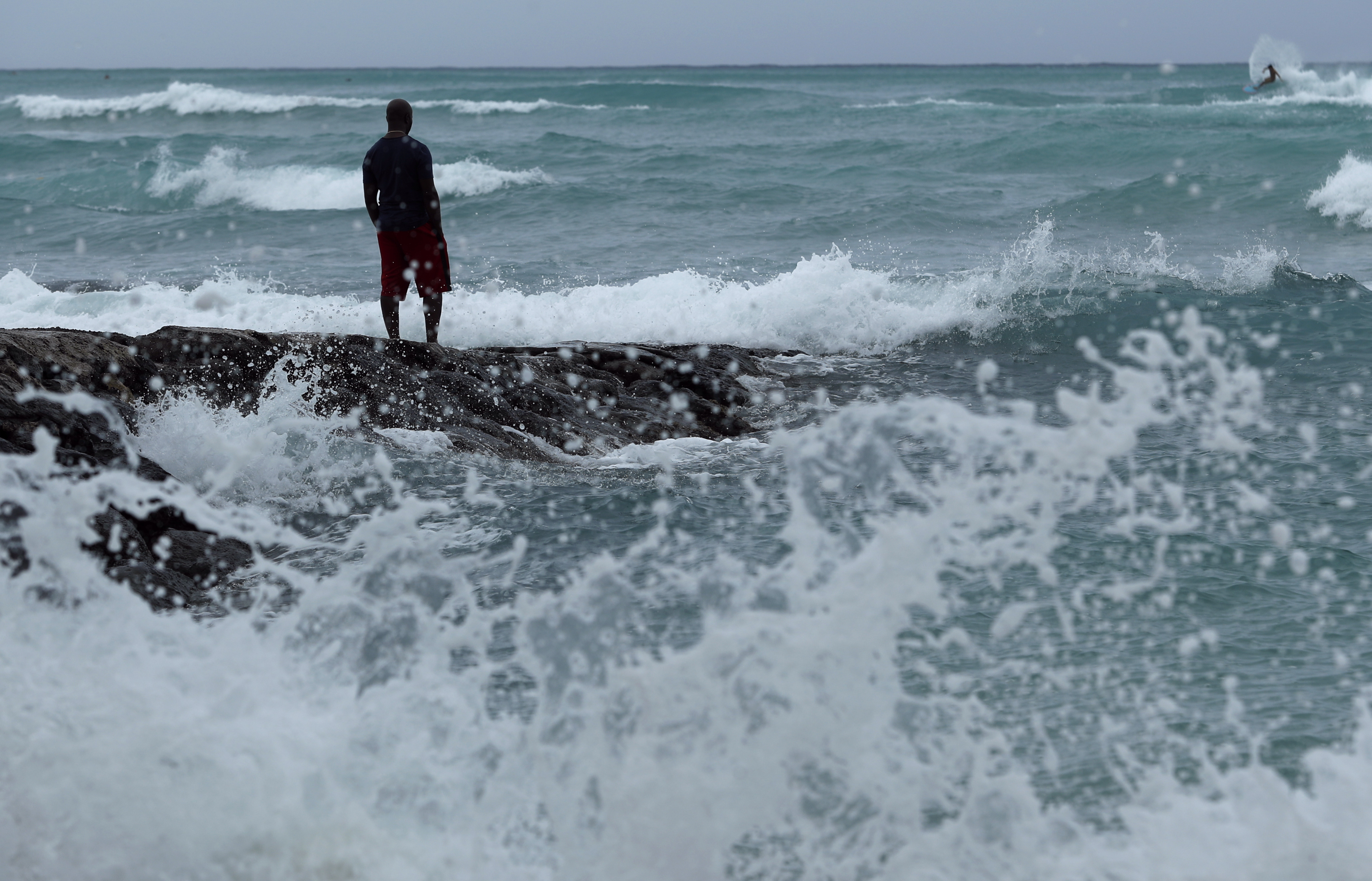 A man stands along the beach as waves crash on shore in Honolulu, Hawaii on Thursday