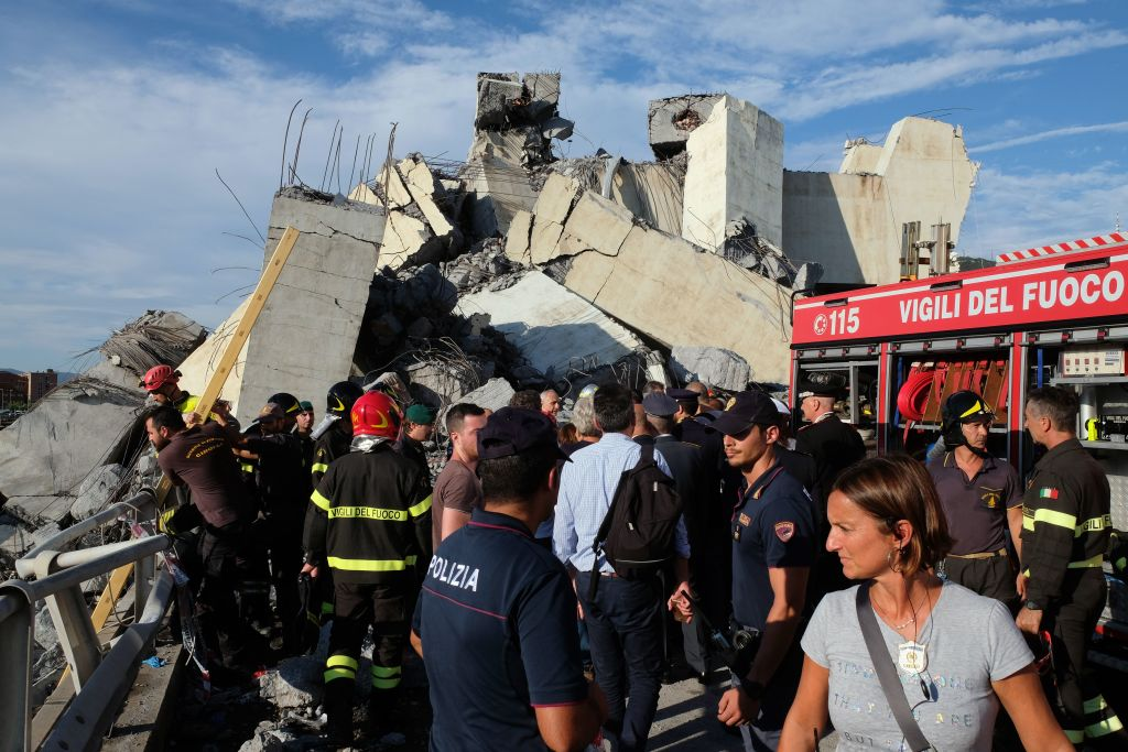 Rescuers inspect the rubble and wreckages near the Morandi motorway bridge after a section of the bridge collapsed in Genoa on August 14, 2018.