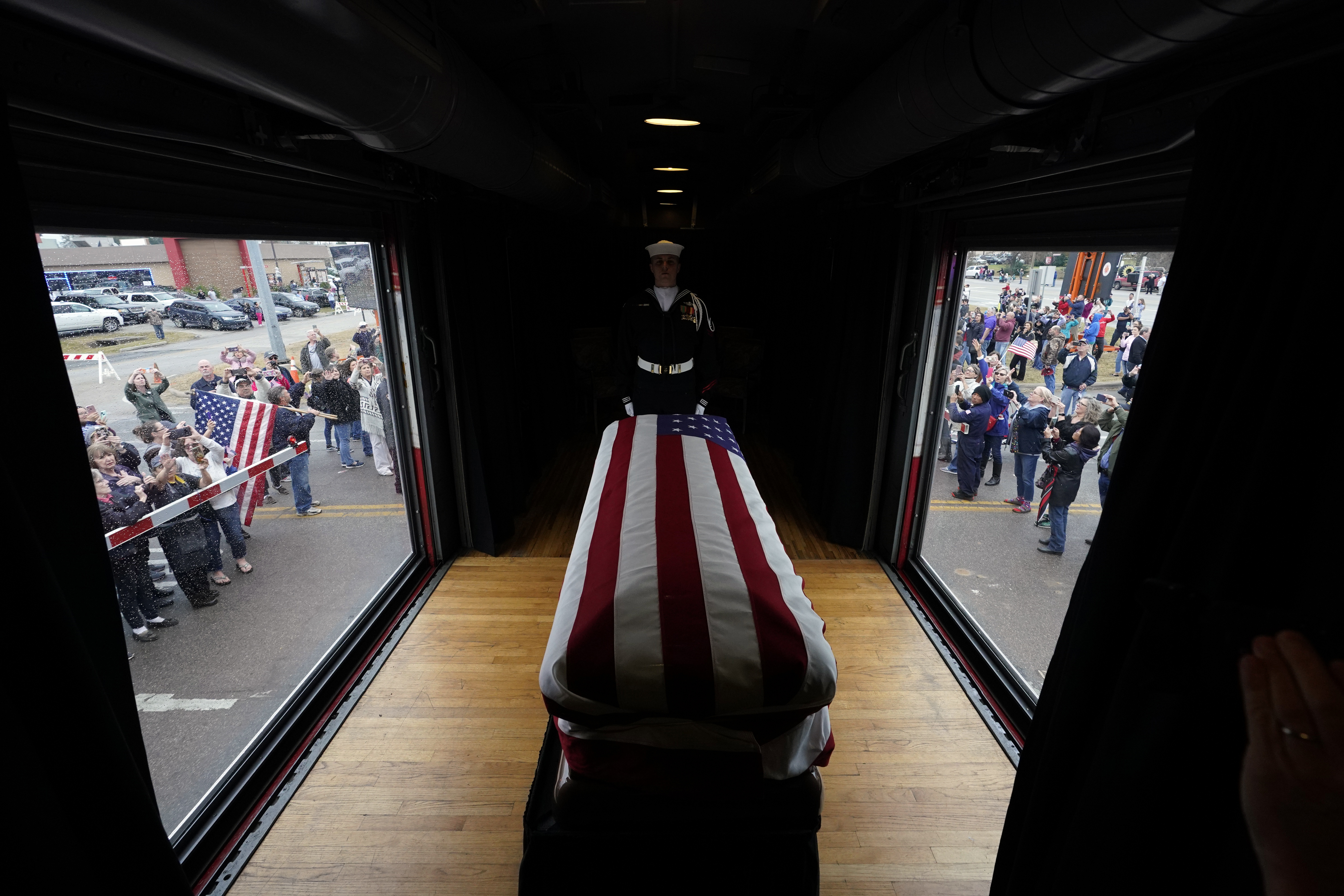 The flag-draped casket of former President George H.W. Bush passes through Magnolia, Texas, Thursday, along the train route to College Station, Texas.