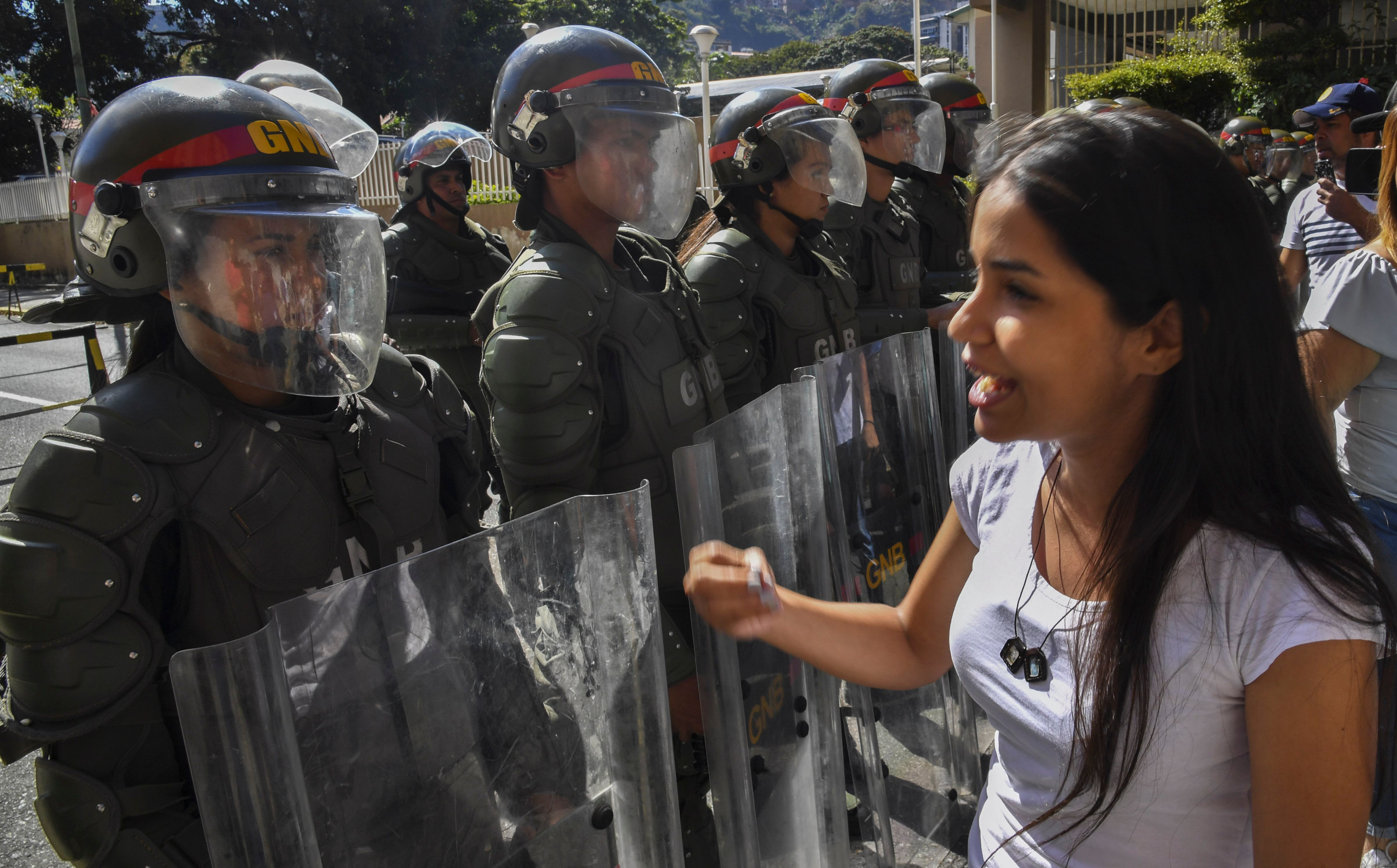 Members of the Bolivarian National Guard stand guard near the main entrance of the forces' headquarters in Caracas as supporters of Venezuela's National Assembly head and self-proclaimed acting president Juan Guaido distribute copies of amnesty measures for anyone in the military who disavows President Nicolas Maduro.
