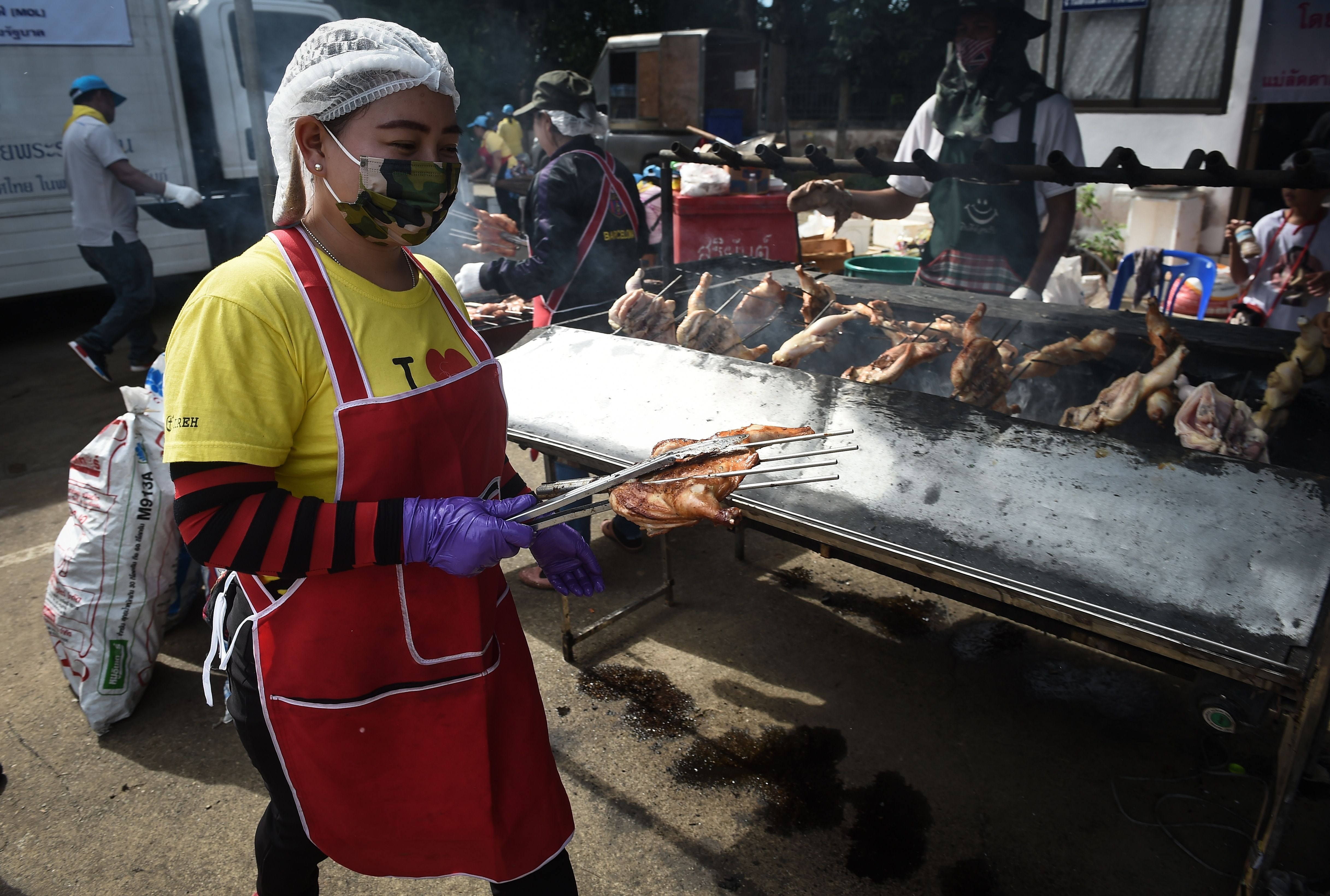 A woman cooks grilled chicken to be packed for volunteers and rescue personnel during a rescue operation.