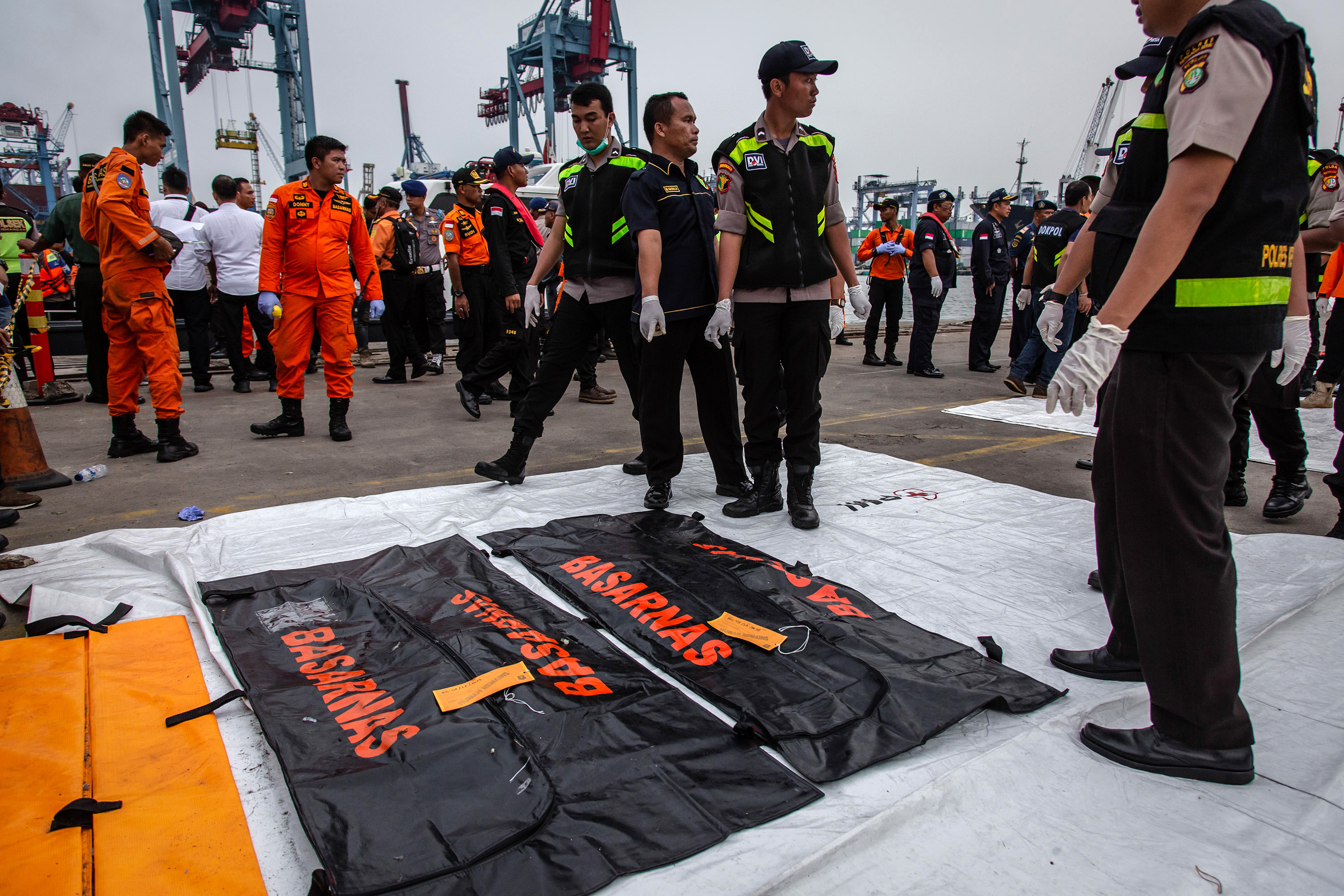 Indonesian police prepare to carry body bags containing remains of a passenger as they recover bodies and personal items from Lion Air flight JT 610 at the Tanjung Priok port Tuesday in Jakarta.