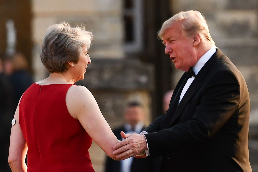Britain's Prime Minister Theresa May (L) shakes hands with US President Donald Trump (R) as she welcomes Trump and his wife US First Lady Melania Trump for a black-tie dinner with business leaders at Blenheim Palace on July 12, 2018.