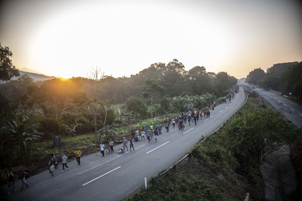 Honduran migrants heading in a caravan to the US, walk alongside the road in Huixtla on their way to Mapastepec, Mexico, on Oct. 24, 2018.