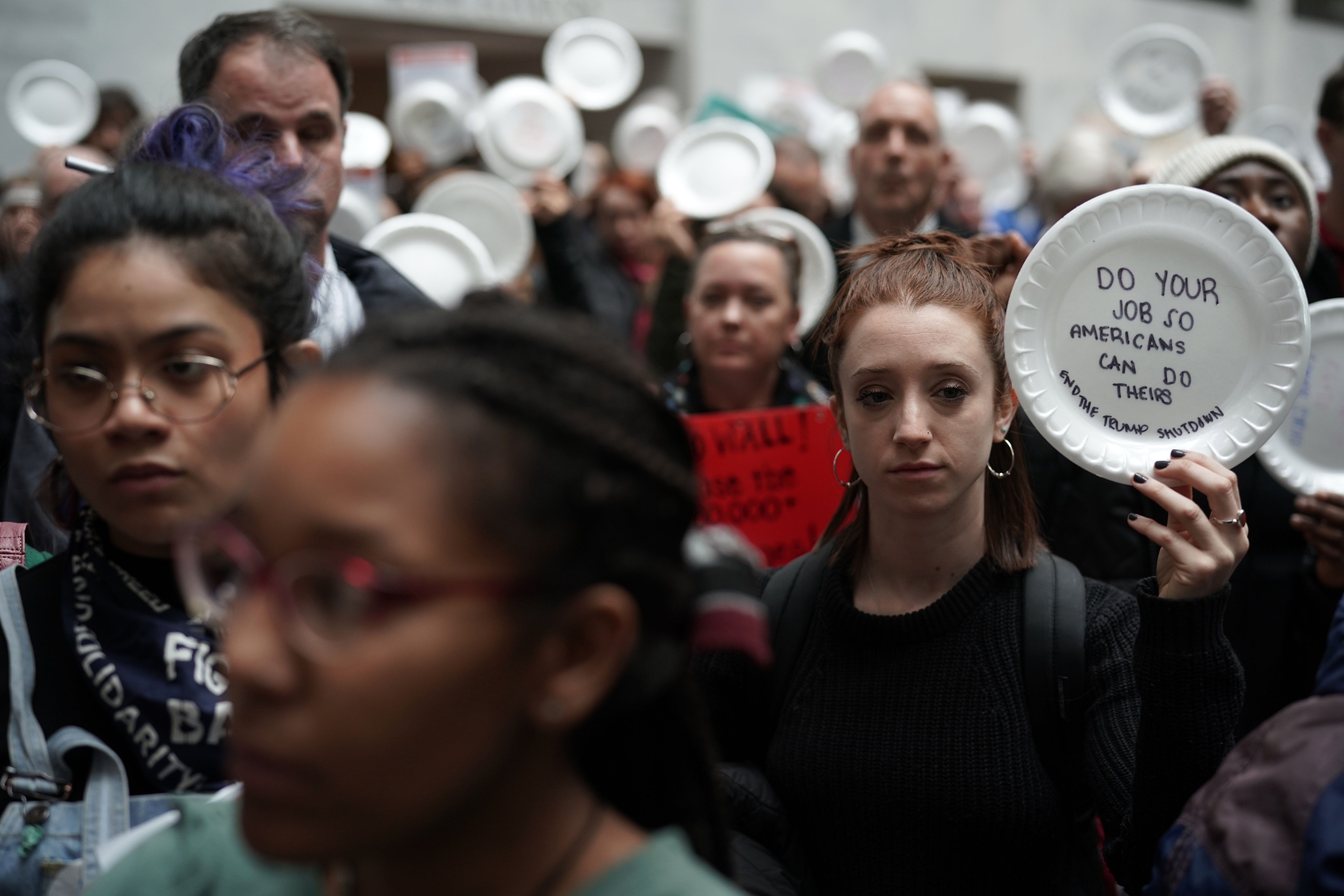Federal employees hold up signs made with styrofoam plates during a protest at the atrium of Senate Hart Office Building.