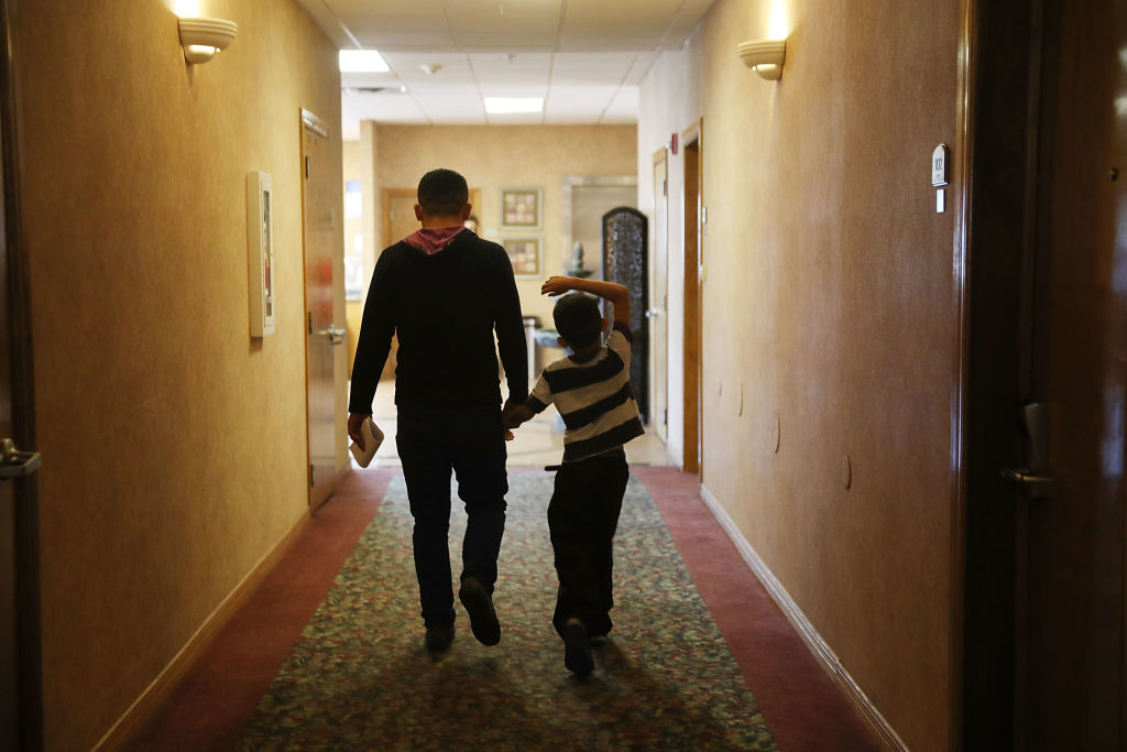 A father and son walk together as they are cared for in an Annunciation House facility after they were reunited with each other on July 25, 2018 in El Paso, Texas.